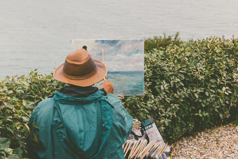 man painting body of water in front of bushes
