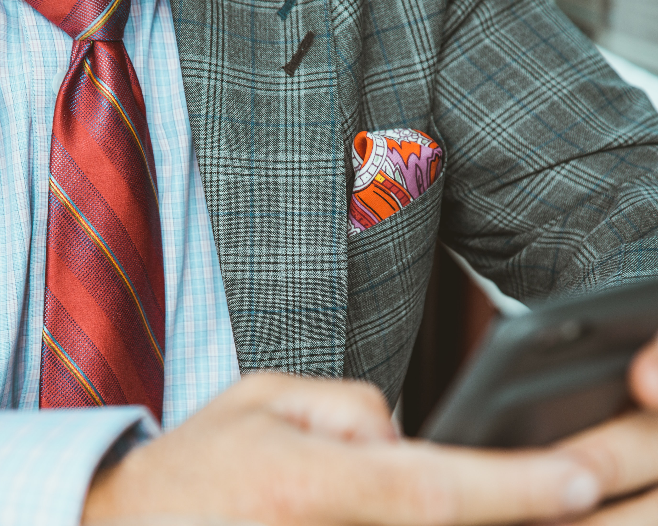 Close-up of a man in a plaid jacket and a tie using a smartphone