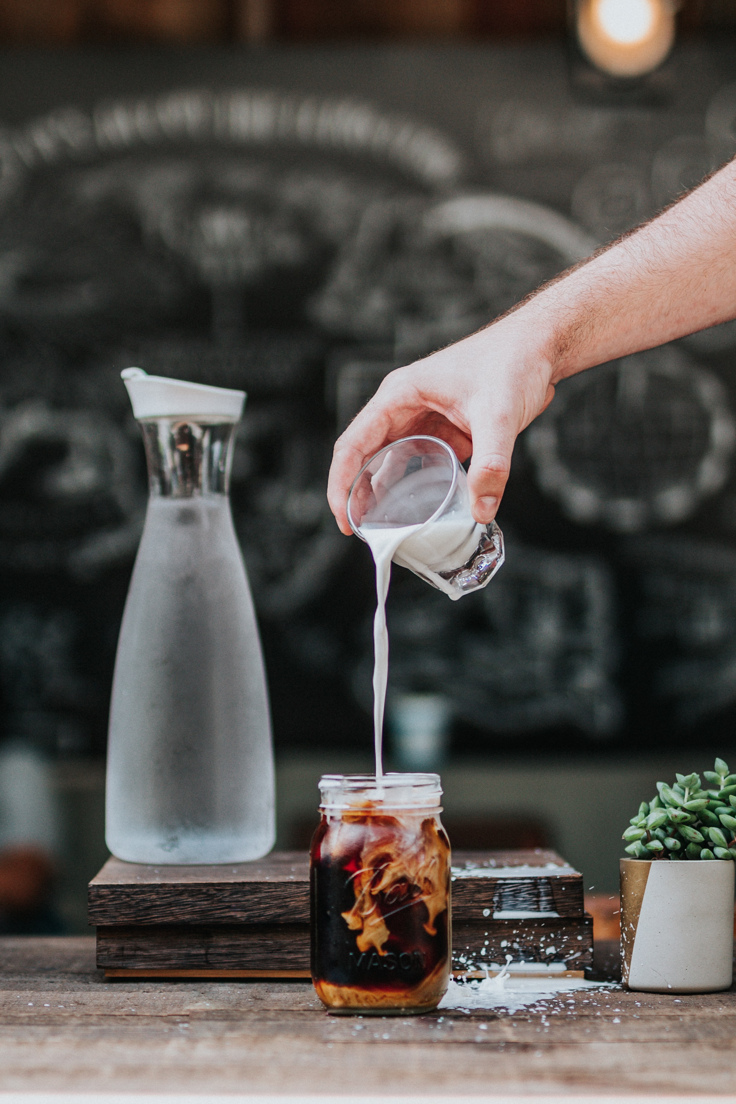 A person pouring milk into a cup of cold brew coffee in a mason jar, in a cafe, on a table with a water jug and succulent plant on it