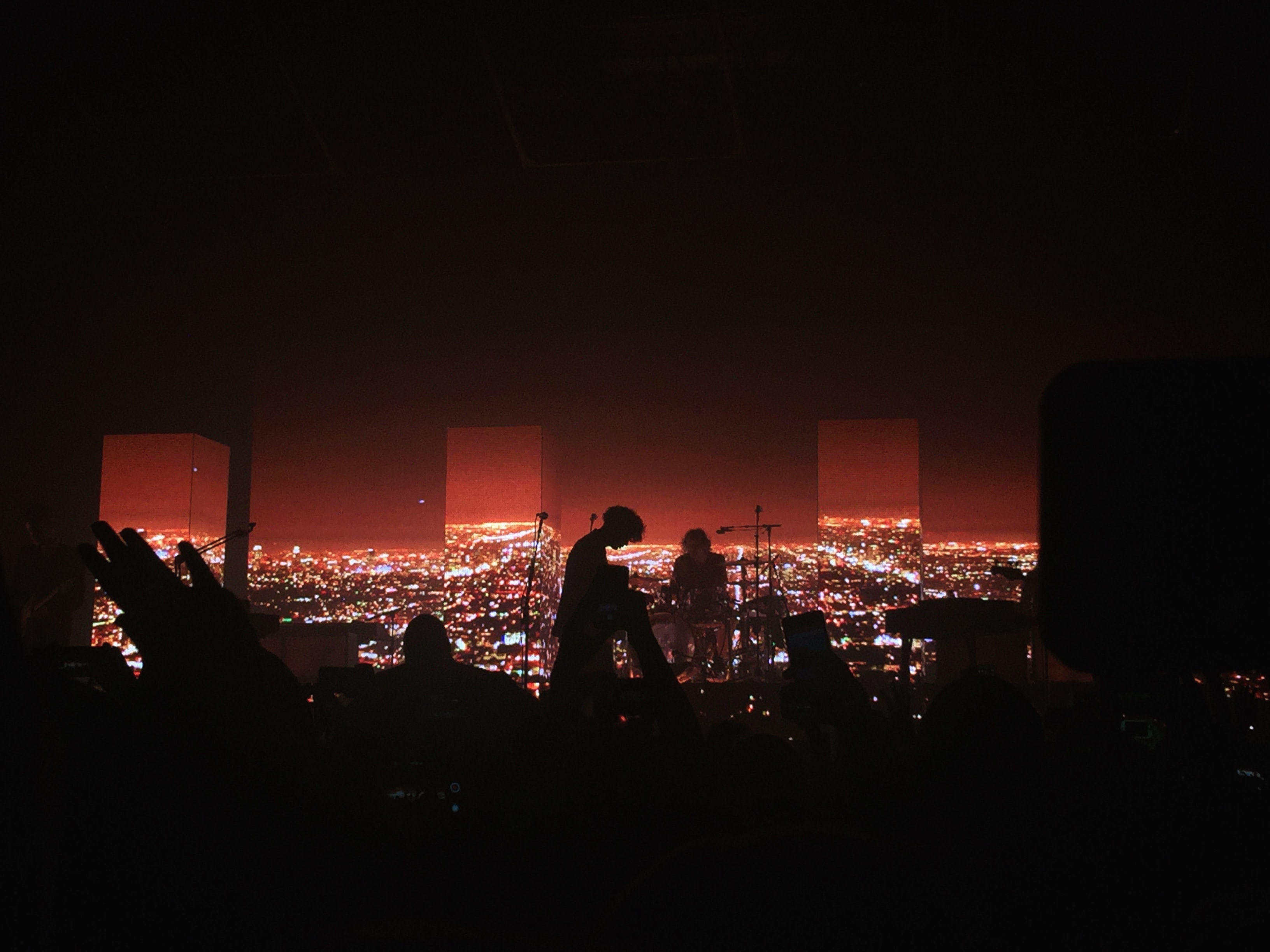 Dark concert venue with silhouetted audience and band in front of red cityscape