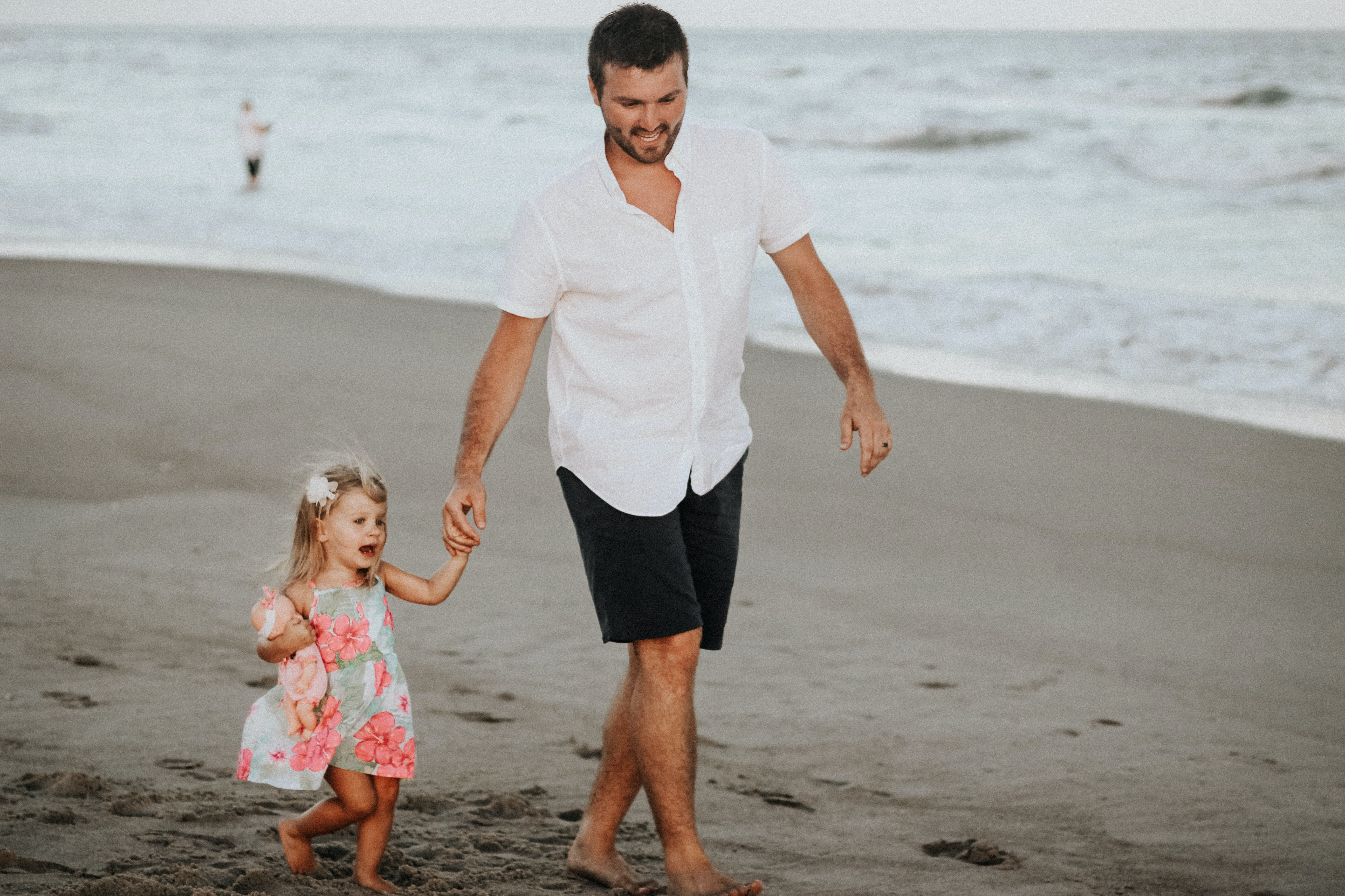 man holding her daughter while walking at the coastline