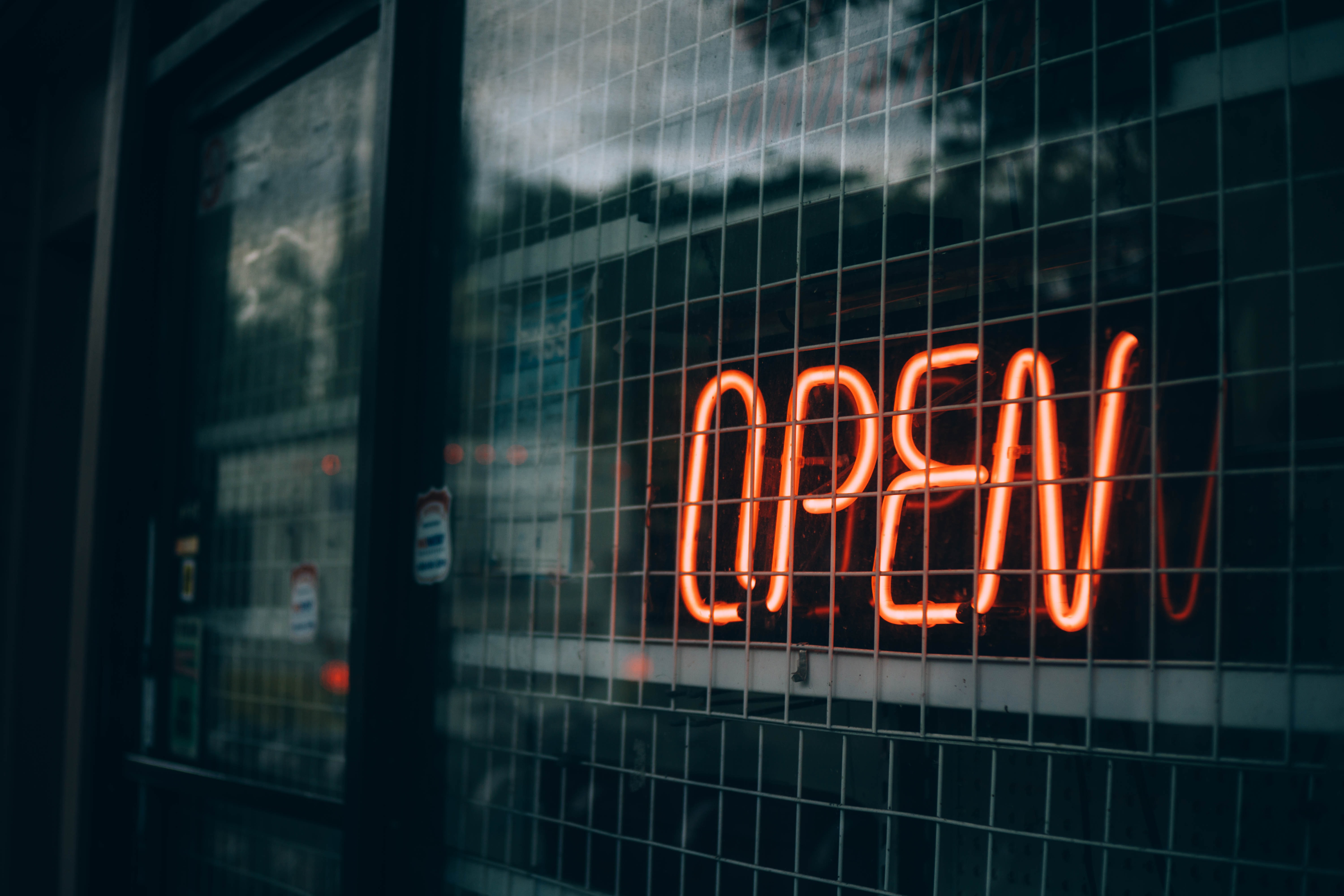 "A neon ""open"" sign at a storefront"