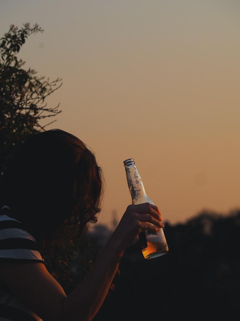 woman holding bottle near bush