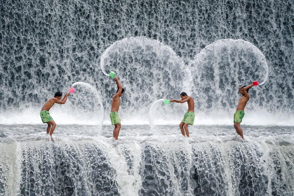 four men throwing dipper of water on waterfalls during daytime