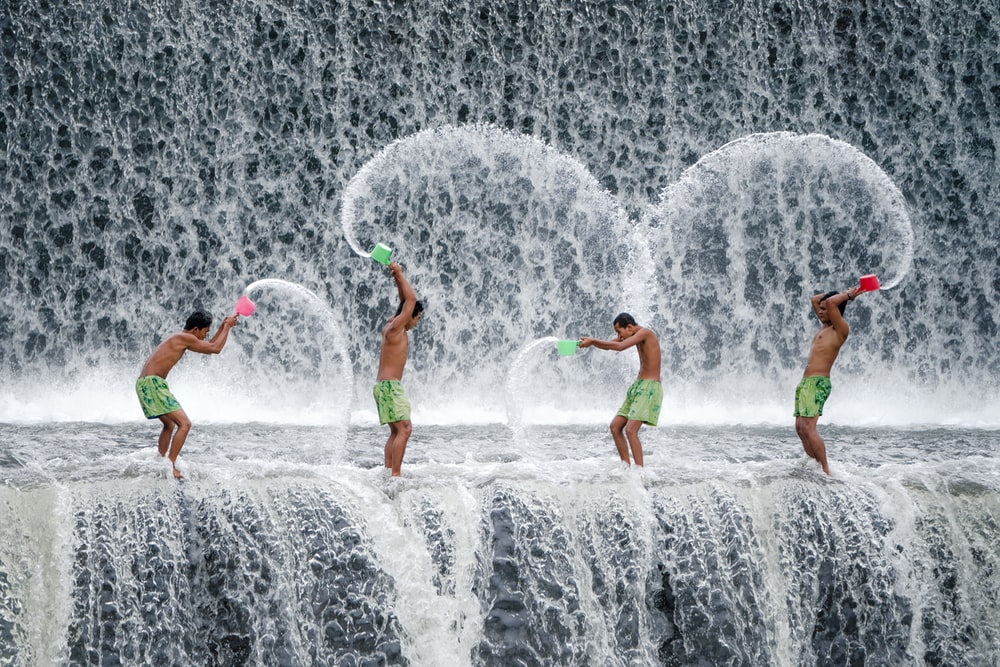 four men throwing dipper of water on waterfalls during daytime