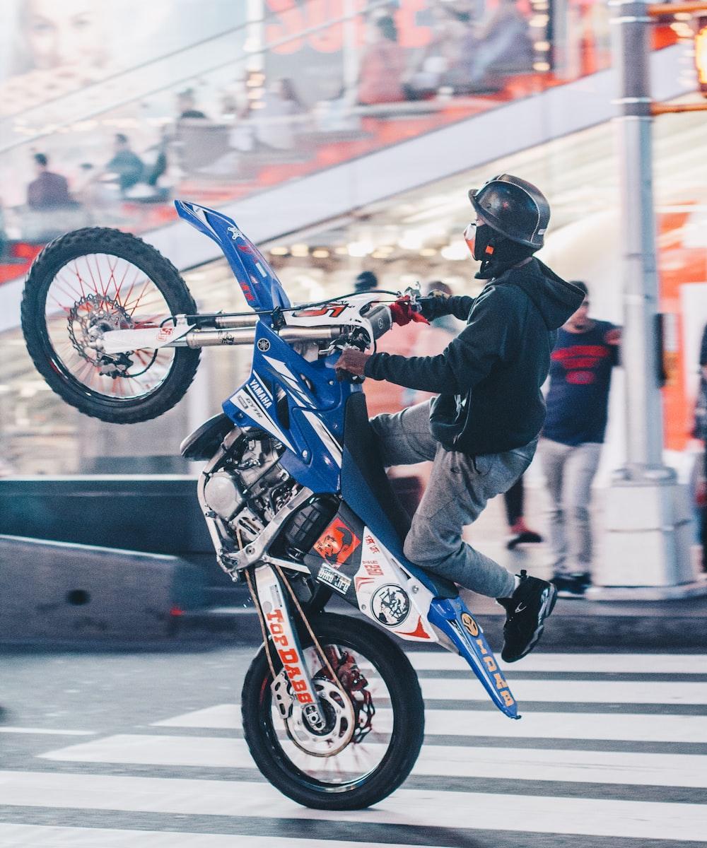 selective focus photography of man doing wheelie on motocross dirt bike