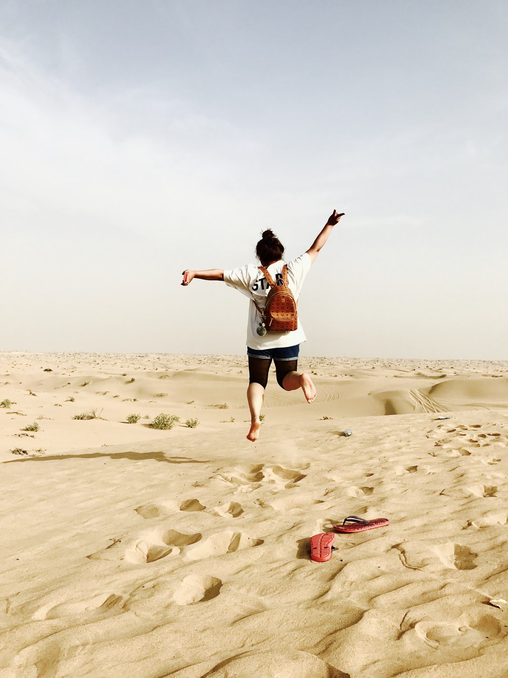 woman jumping on brown sand during daytime
