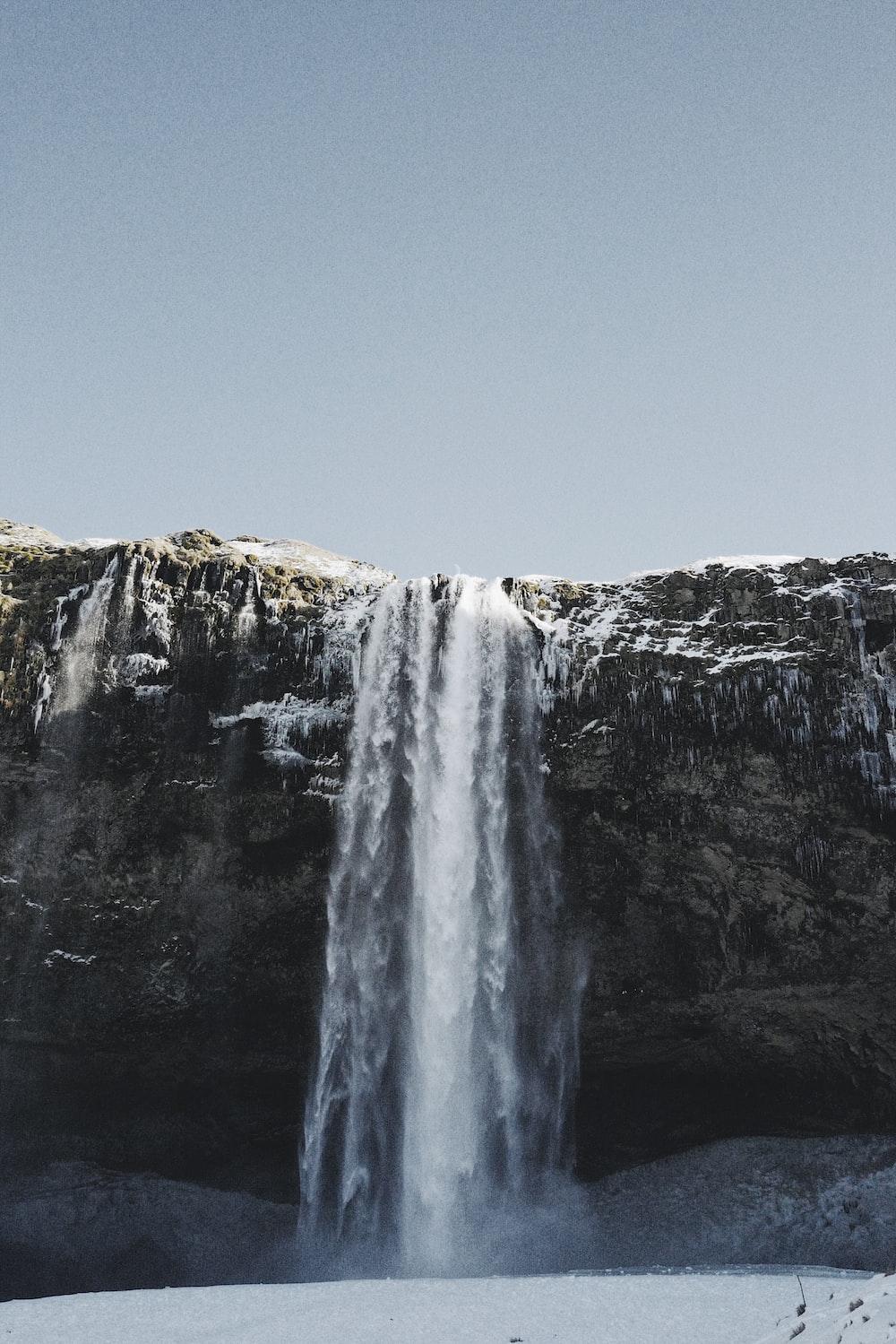 waterfall under blue sky
