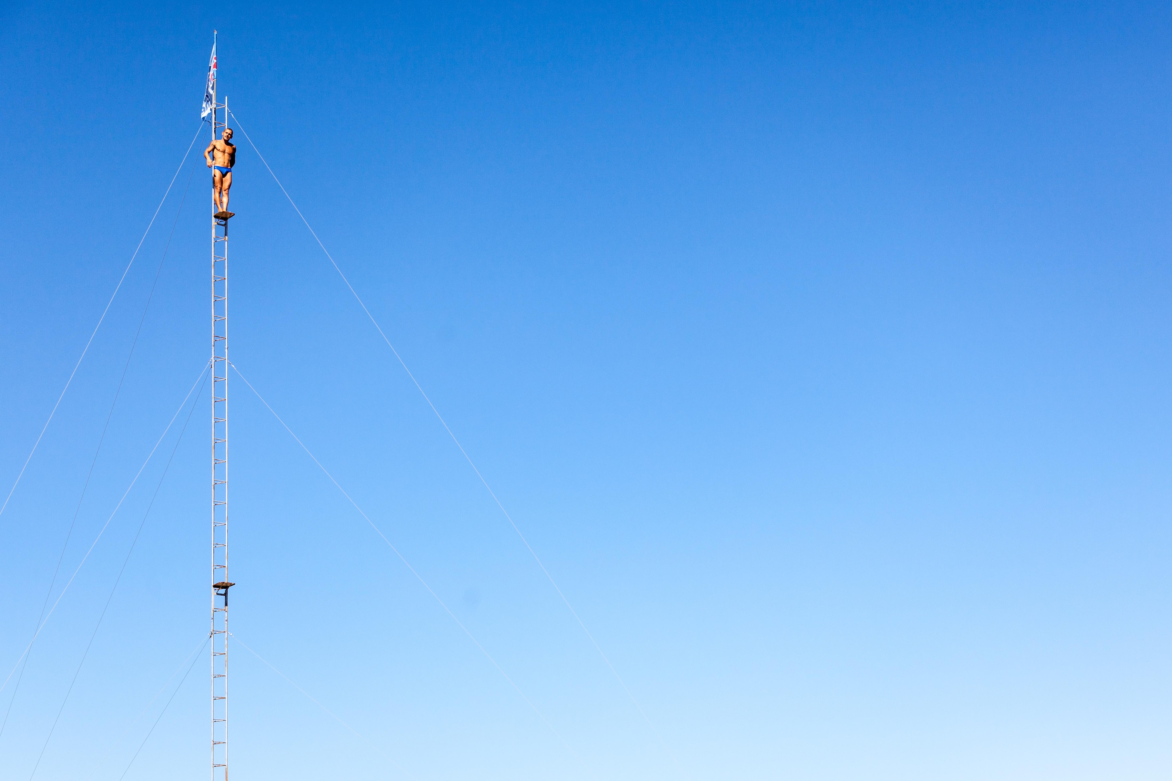 man wearing blue brief standing ladder