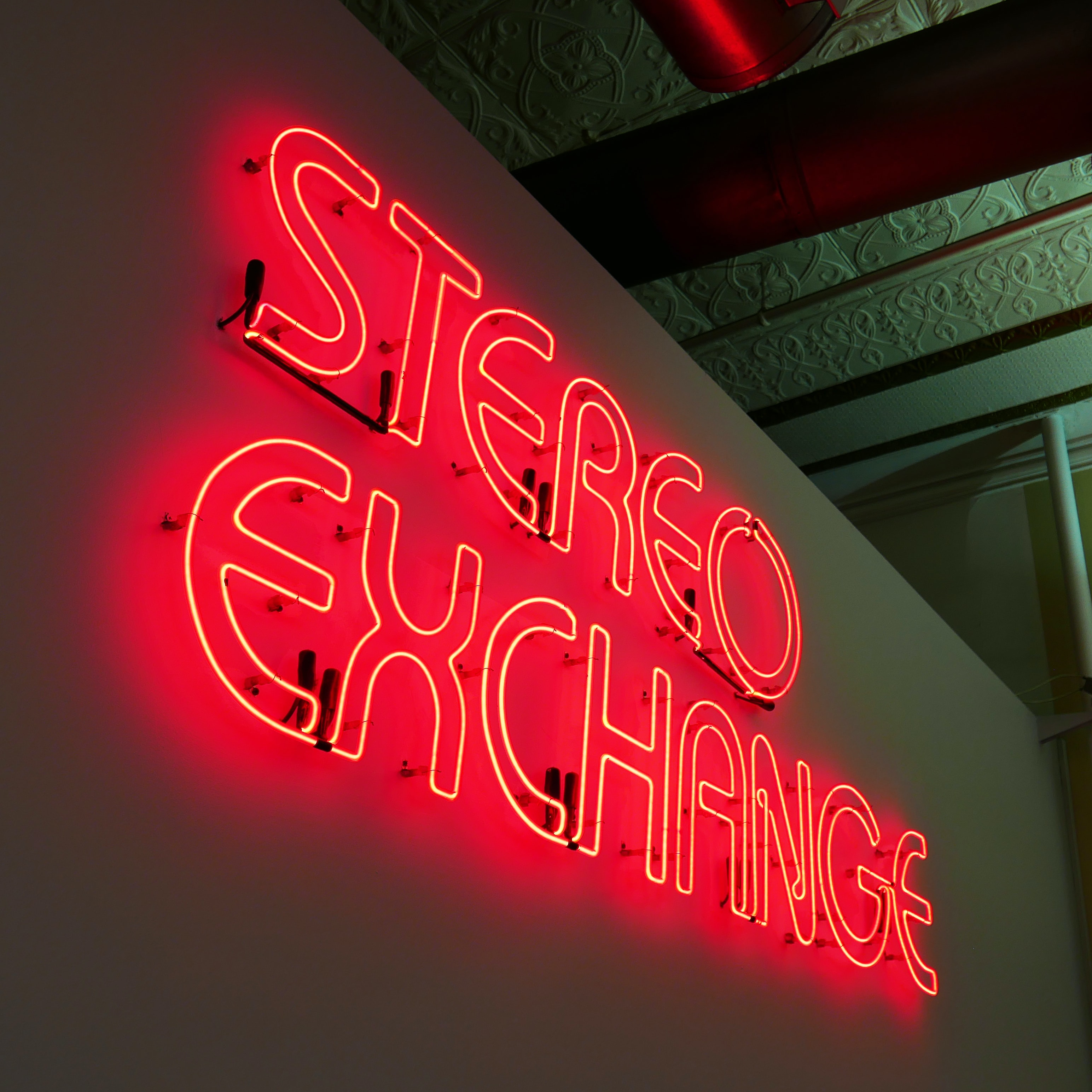 Stereo Exchange LED pub signage on white painted concrete wall