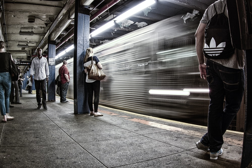 time lapse photography of train beside people on station
