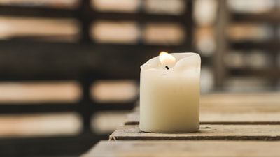selective focus photography of white pillar canle candle teams background