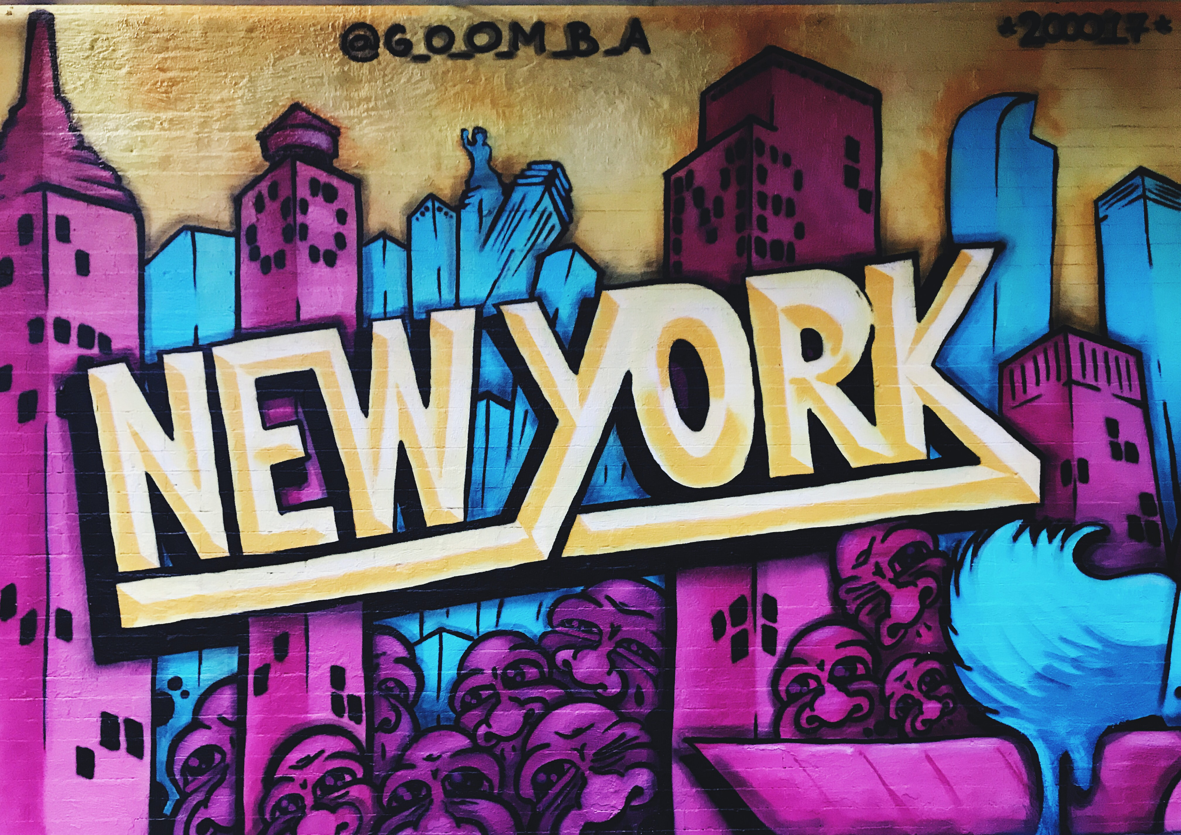 """Graffiti typography says """"New York"""" over colorful city skyline"""