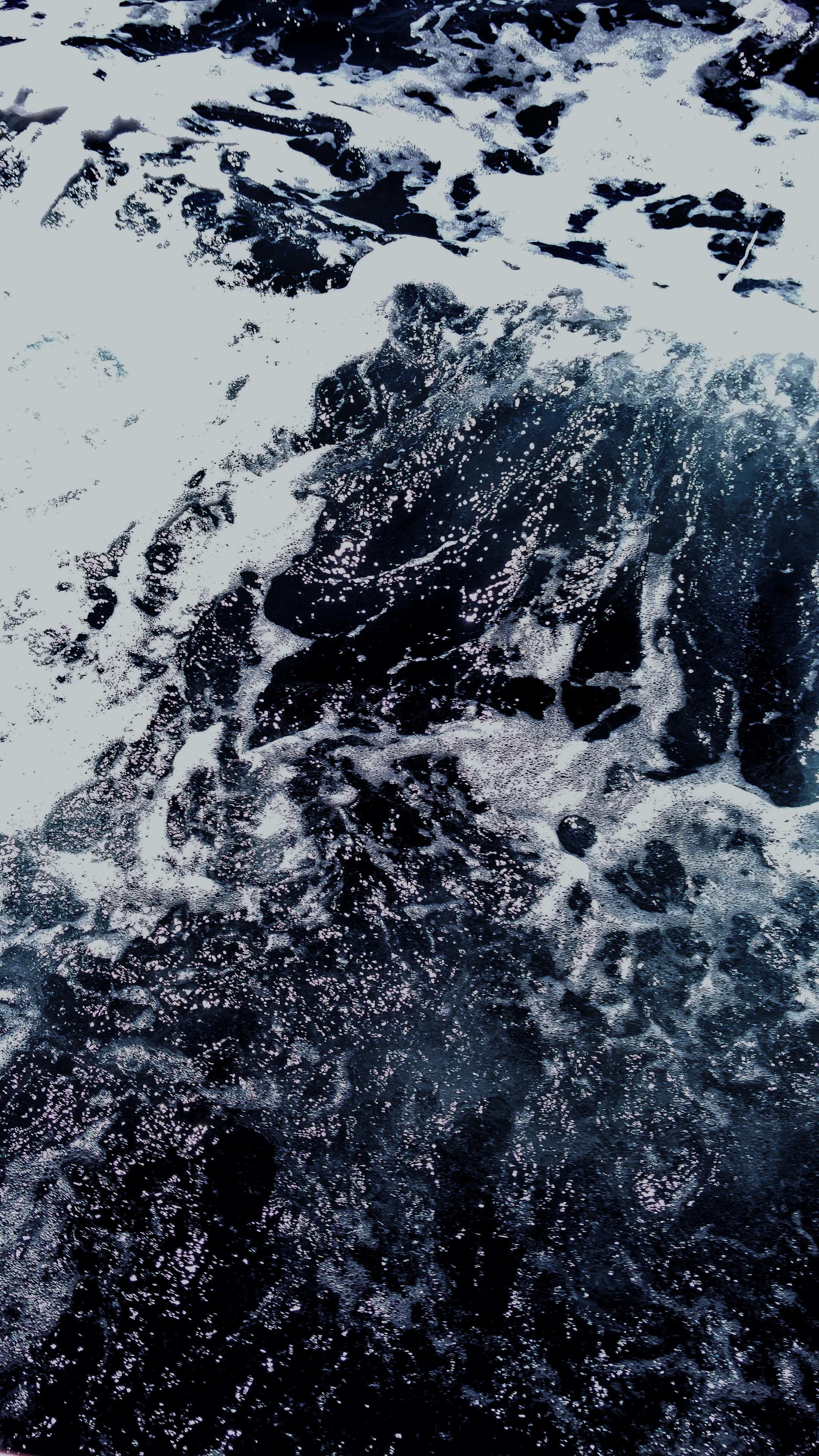 Foam on rough water waver on an ocean shoreline