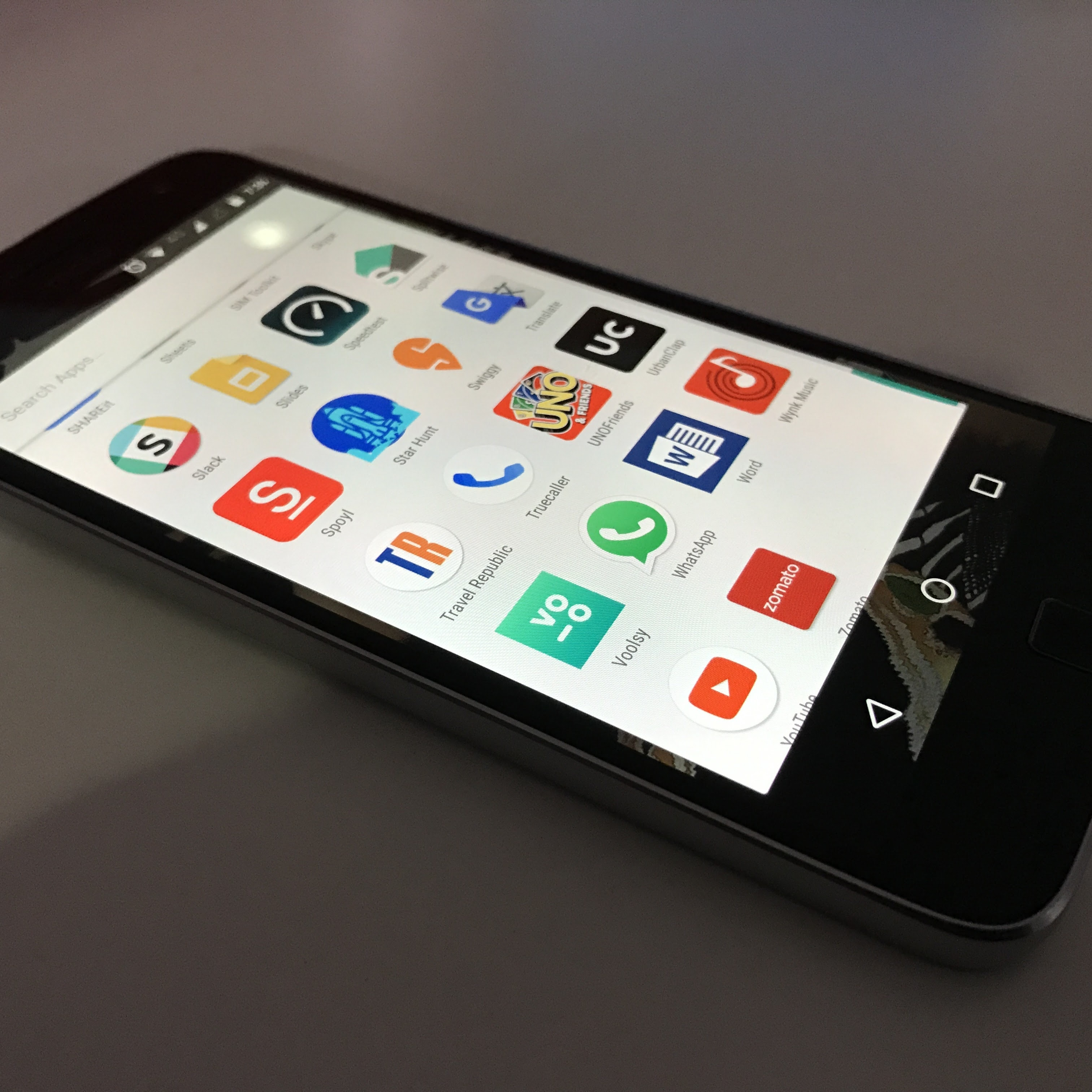 A smartphone with Android with a homescreen showing various apps including Slack, Splitewise, Uno, Word, WhatsApp, and YouTube