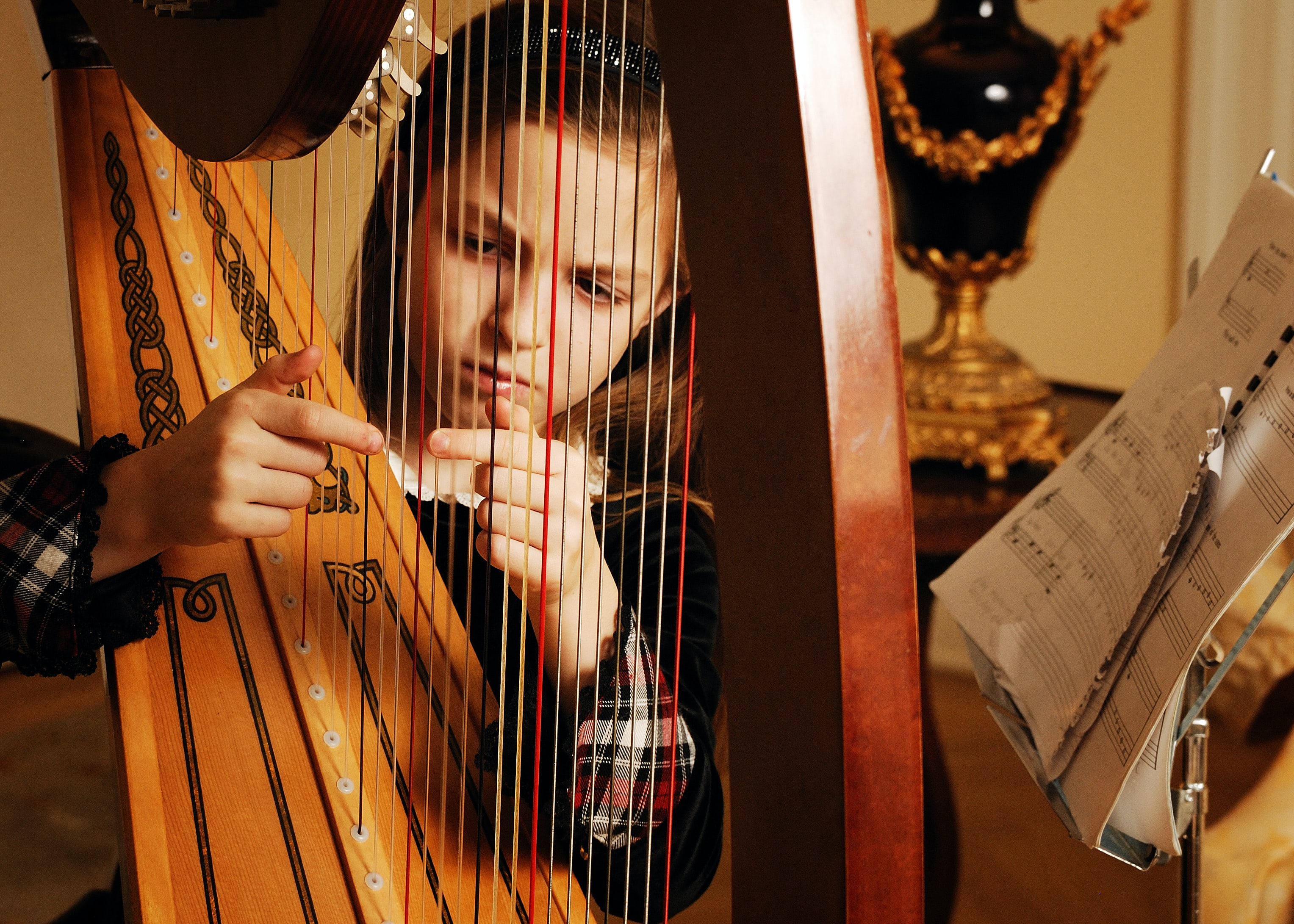 A young girl scowling as she plucks the strings of a grand wooden harp beside a sheet of music on a stand and an expensive looking vase