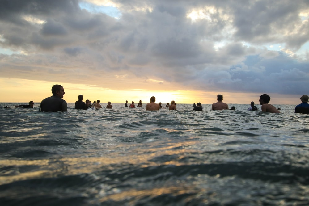 group of people in body of water during sunset