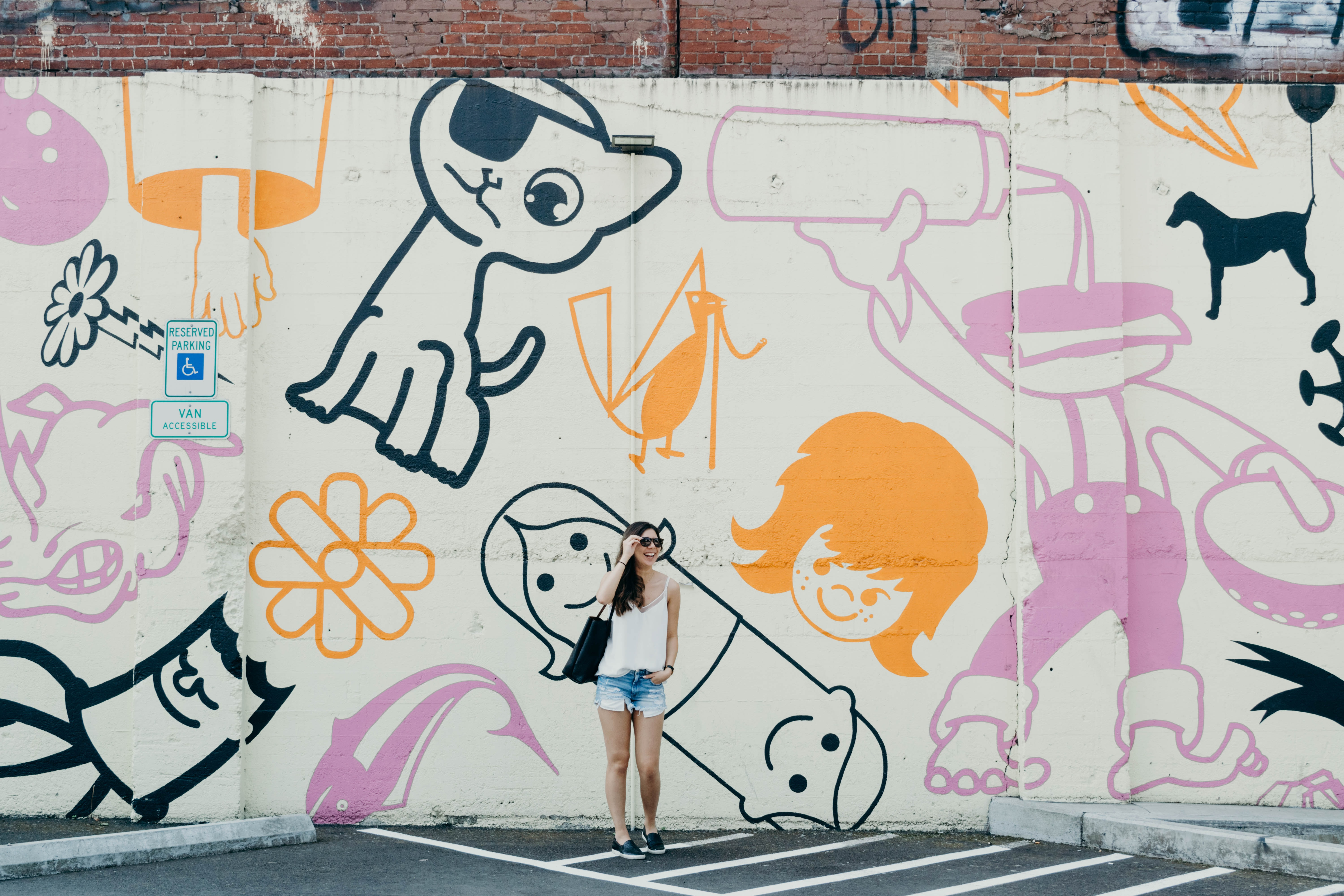 candid photography of woman standing against graffiti wall with broad smile