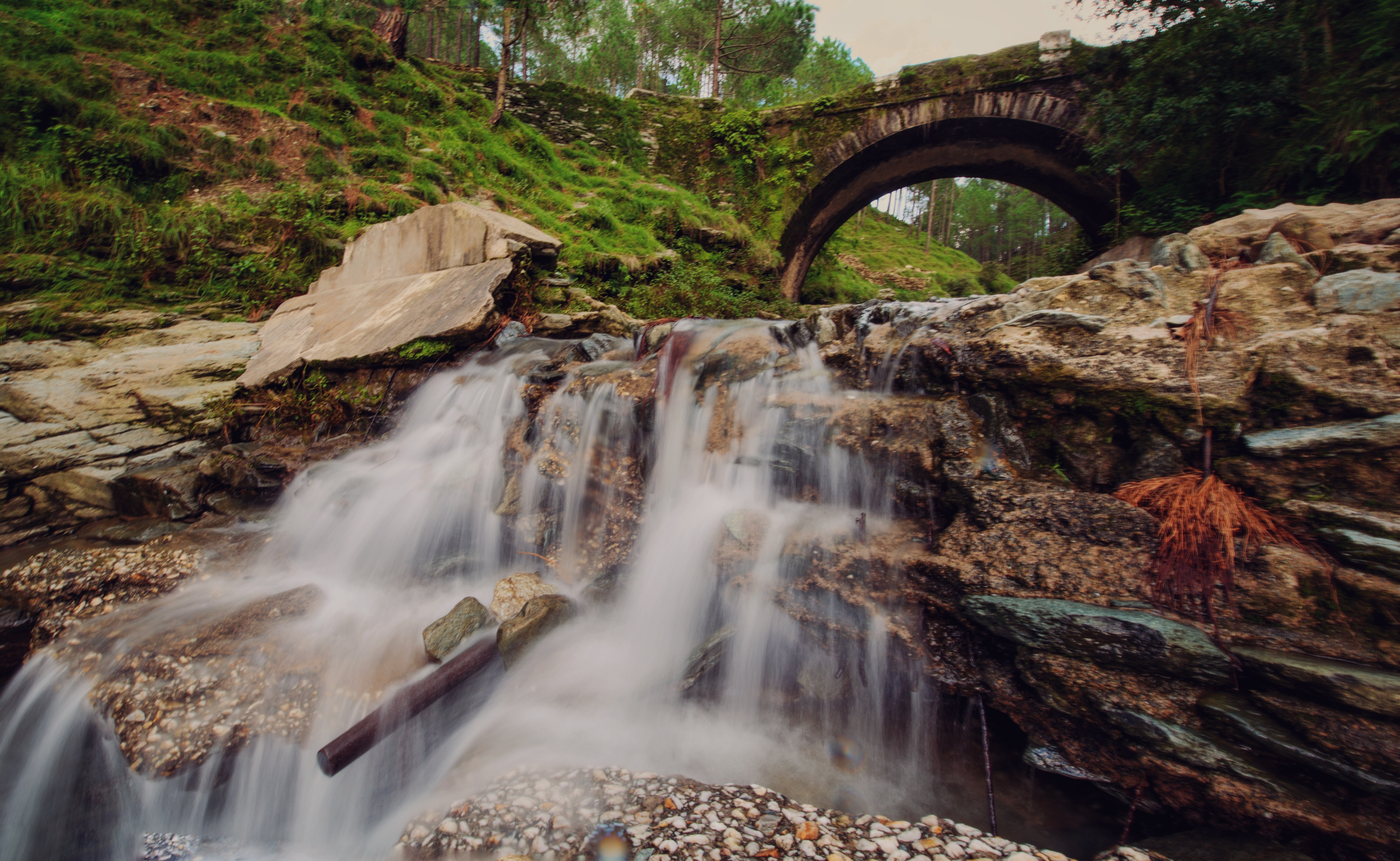 Misty waterfalls rush down cascading rocks in the woods