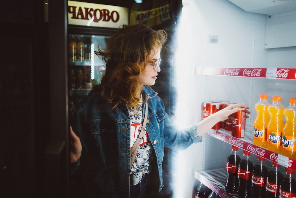 A woman in a jean jacket chooses a drink from refrigerated racks at a market