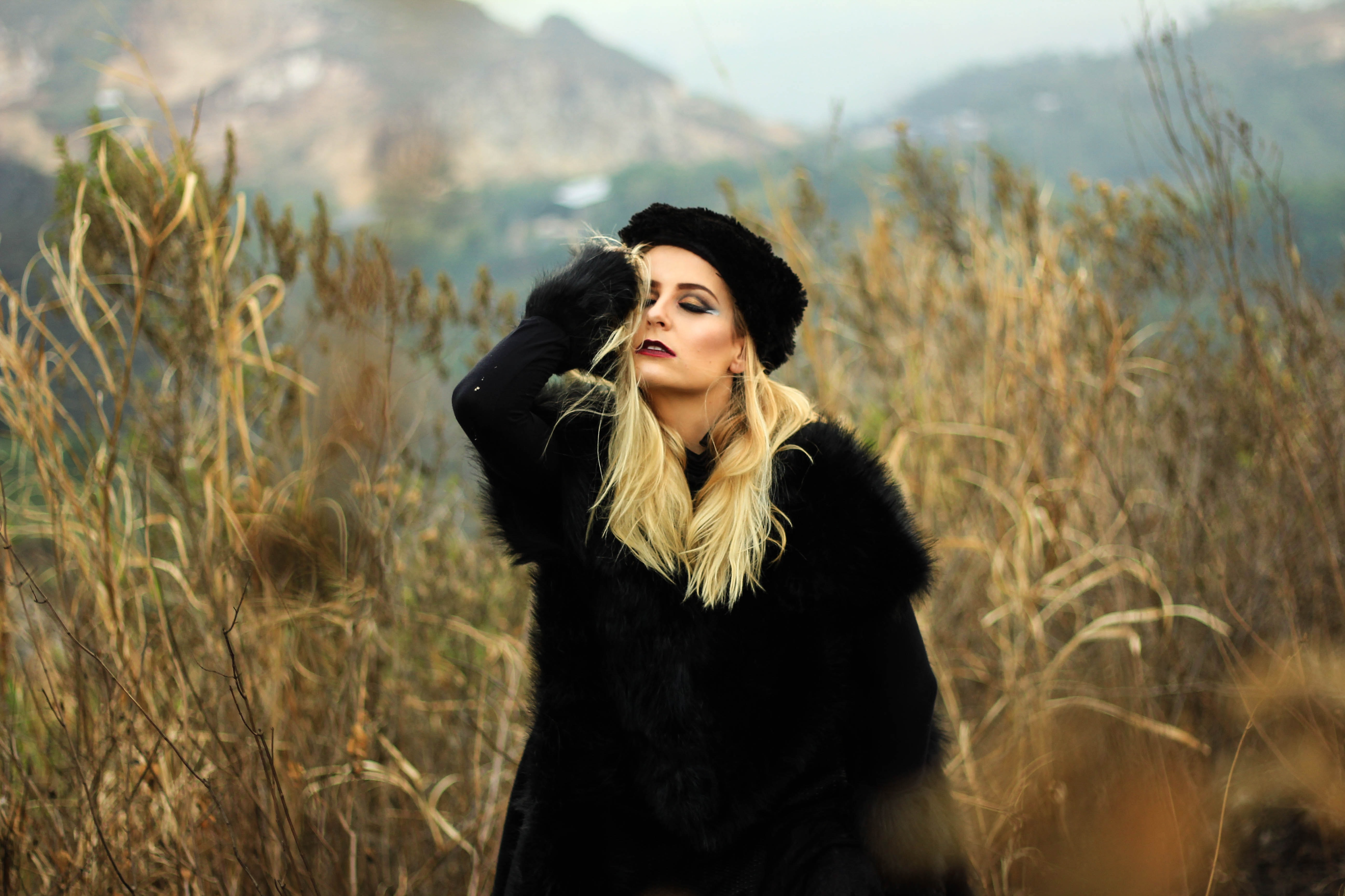 A woman in a black fur coat and hat stands in a field of tall grasses