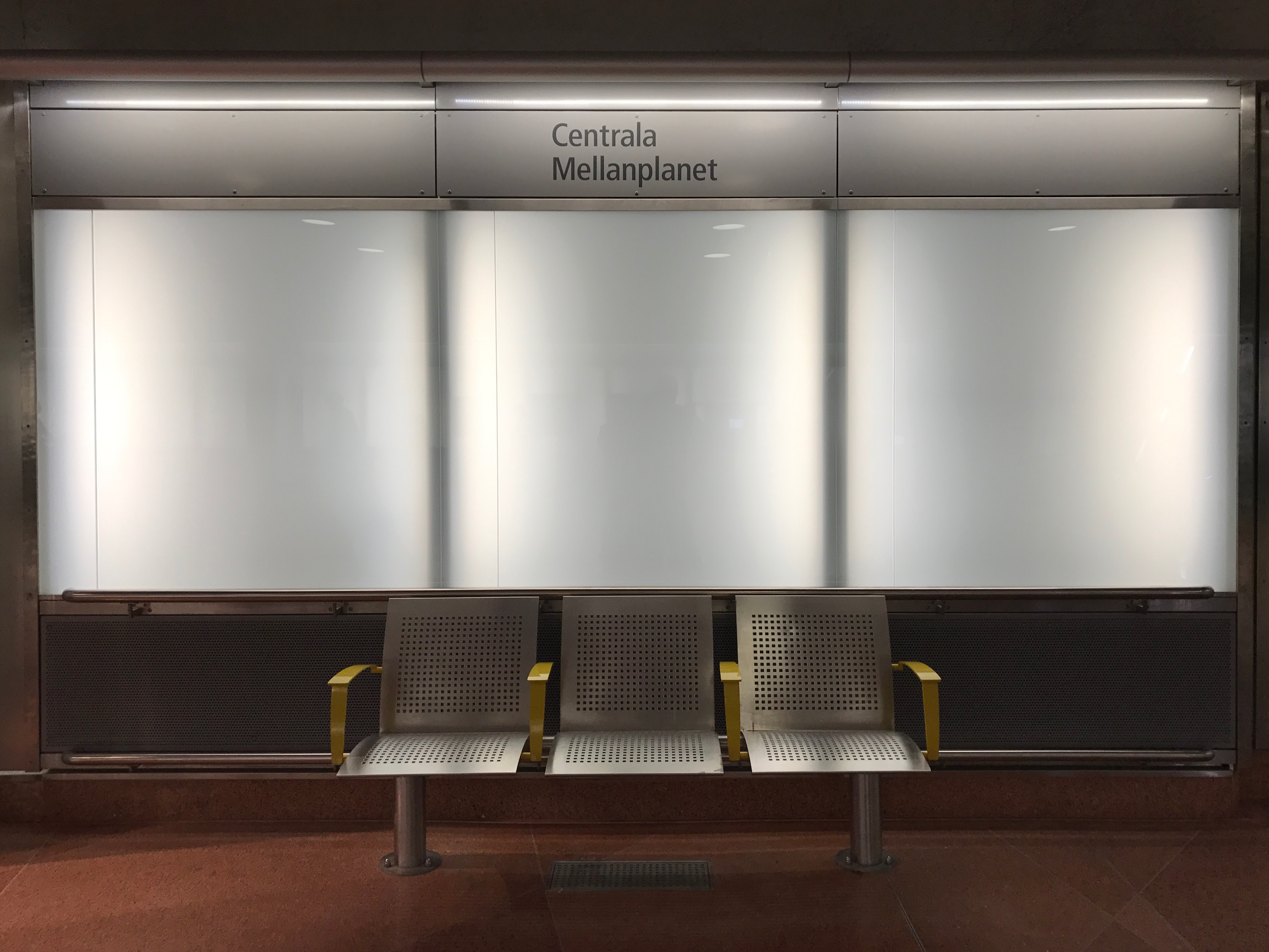 """Underground metro station in subway station in Stockholm with a gray bench and """"Centrala Mellanplanet"""" sign"""