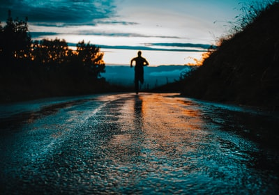 silhouette photo of a person running on road life zoom background