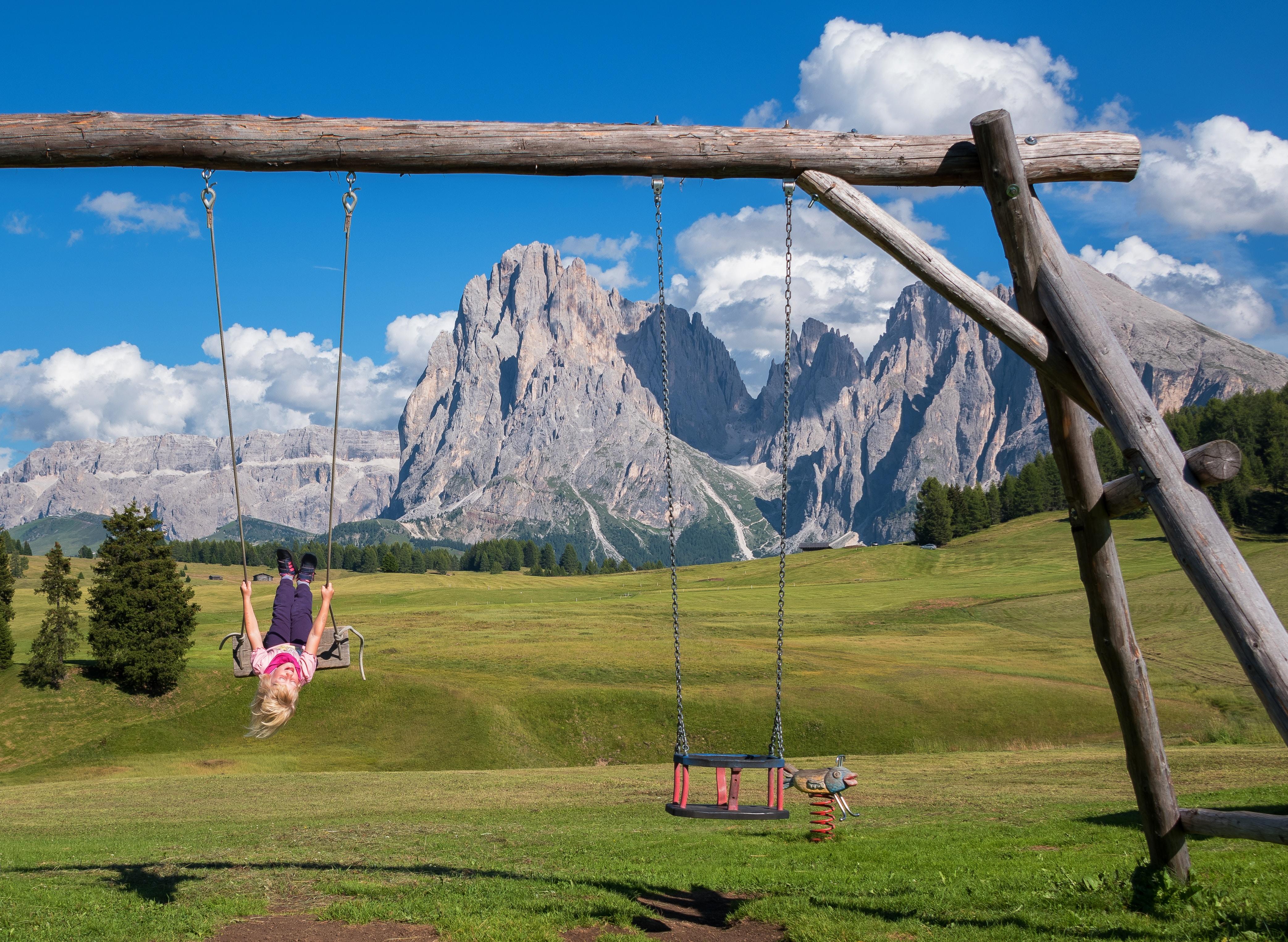 girl riding on swing facing mountain
