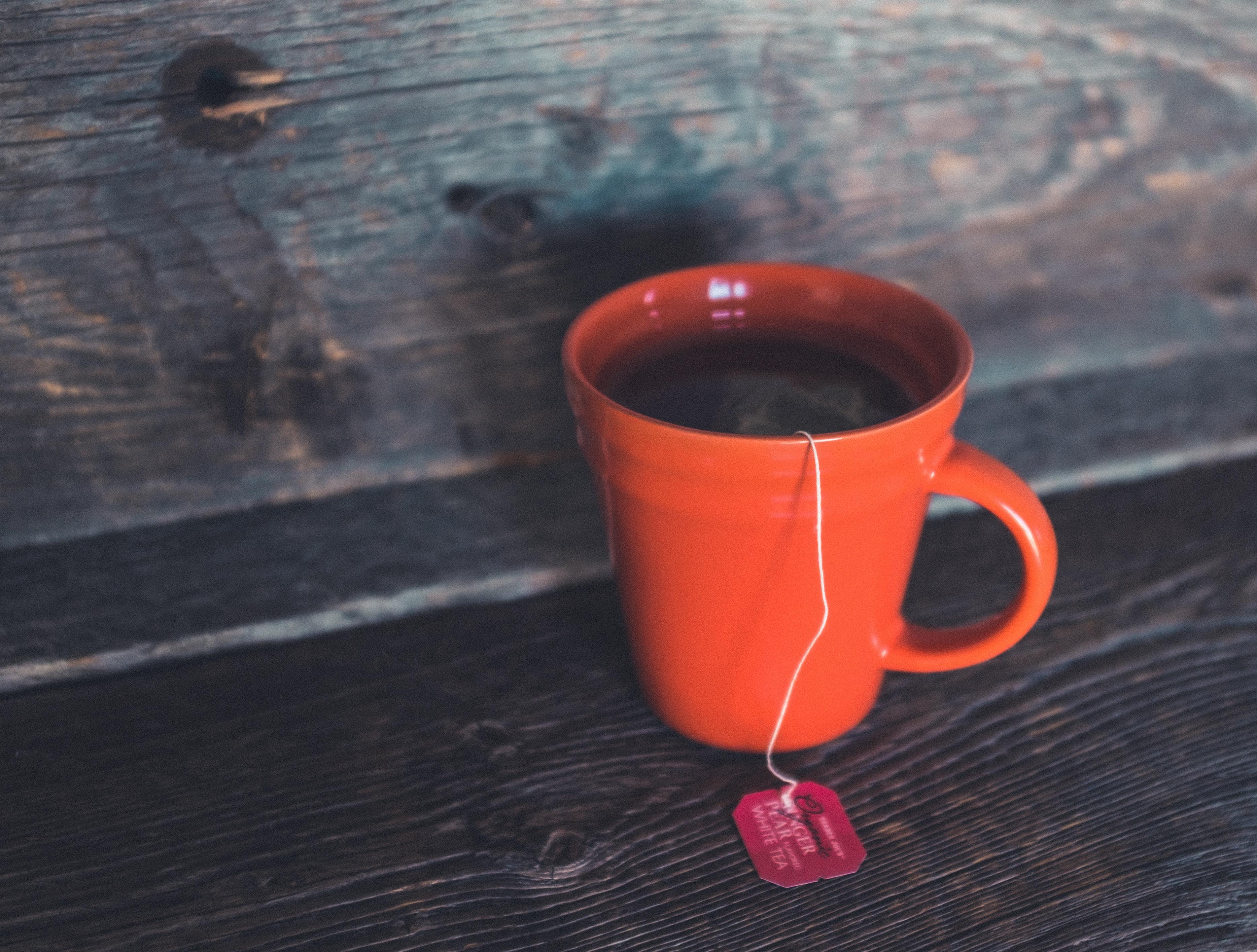orange ceramic teacup on gray bord