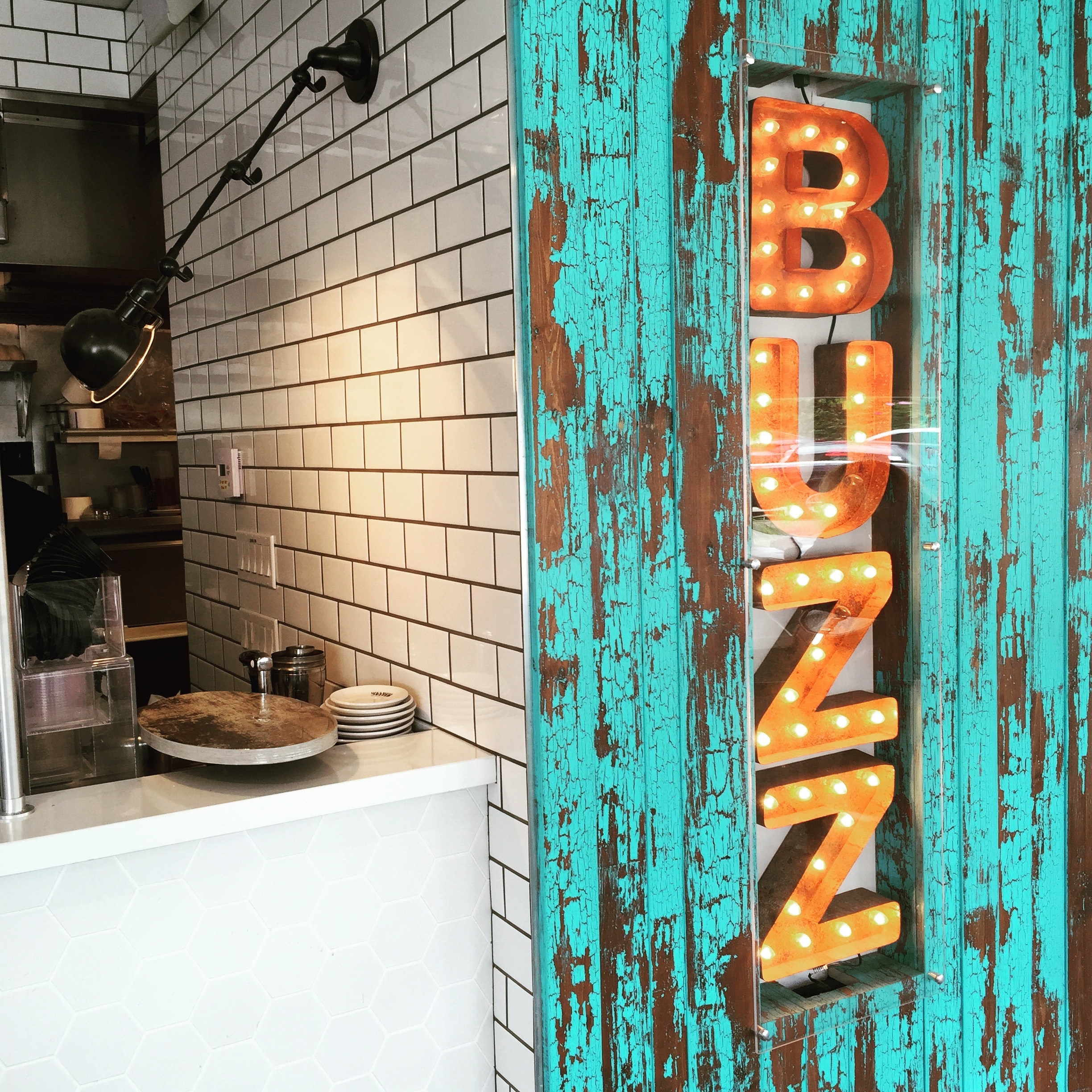 A marquee sign that reads BUZZ installed into a bark textured wood wall beside a white tiled commercial kitchen and serving area