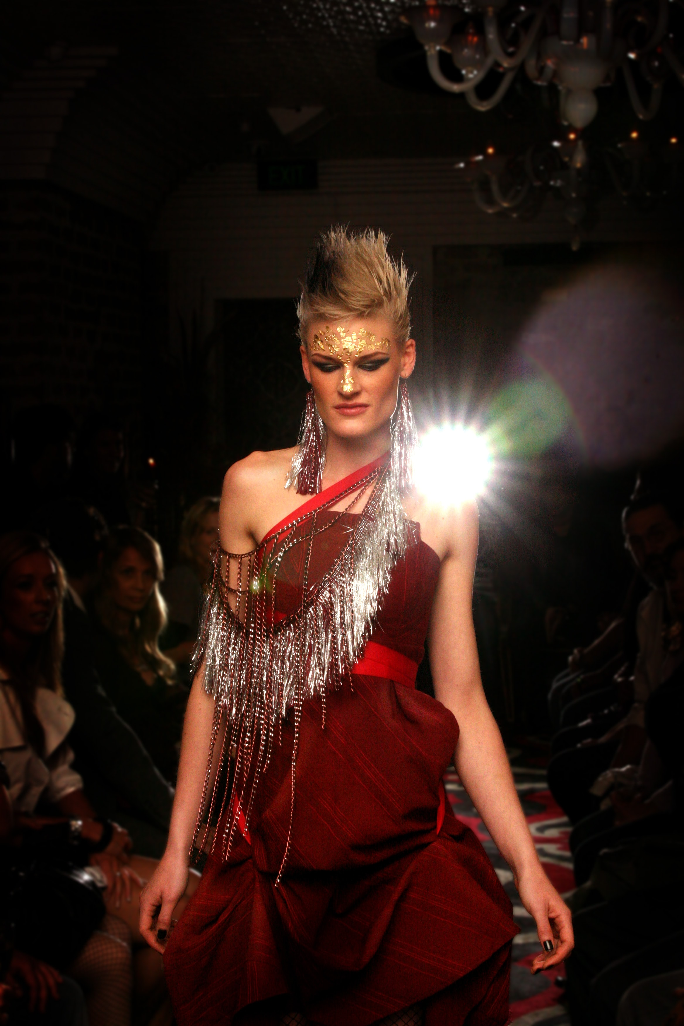 High fashion model in avant garde makeup and clothing walking the runway