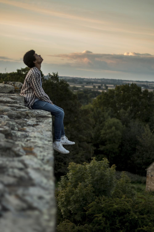 man sitting on gray concrete cliff