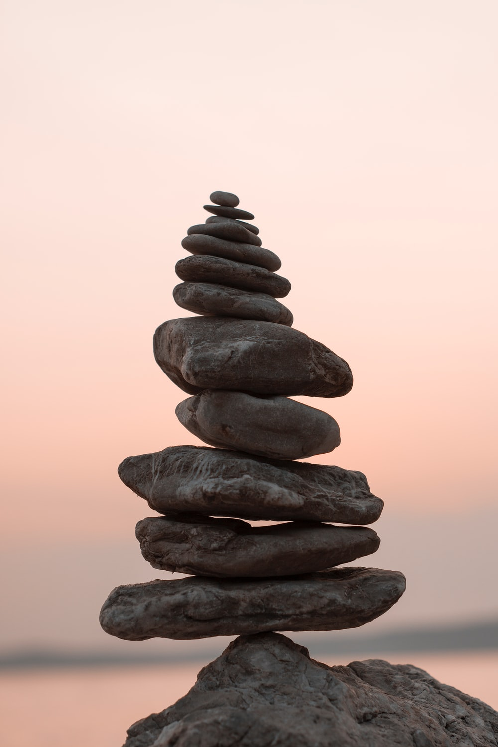A stack of rocks against a pink sky
