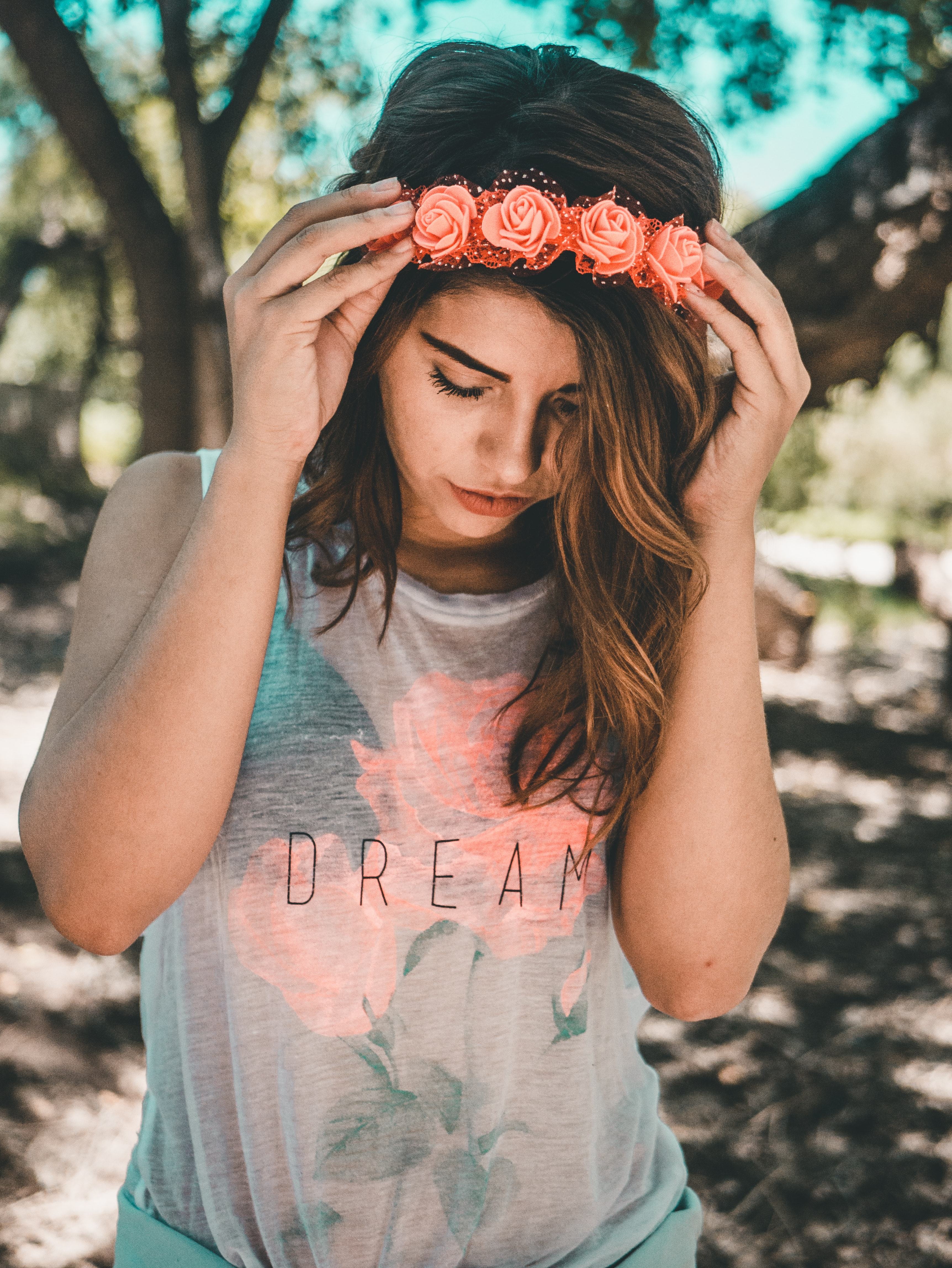 """Whimsical young woman with a flower crown headband and a """"dream"""" shirt"""