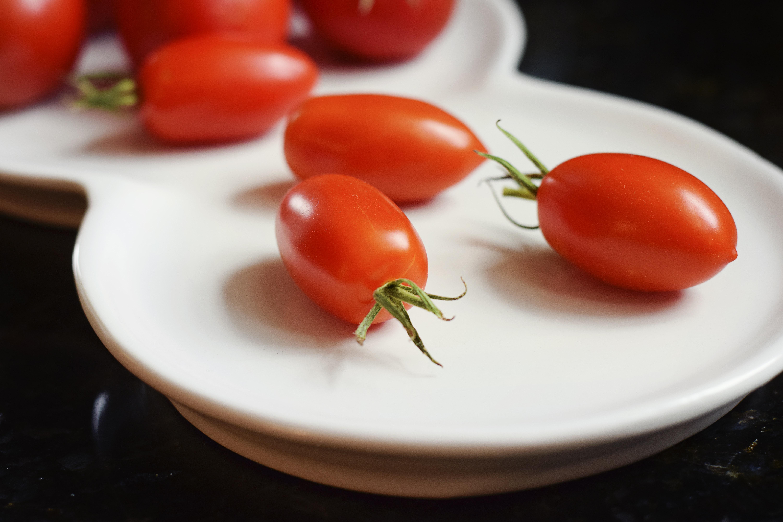 Ceramic platter of fresh roma tomatoes ready to eat