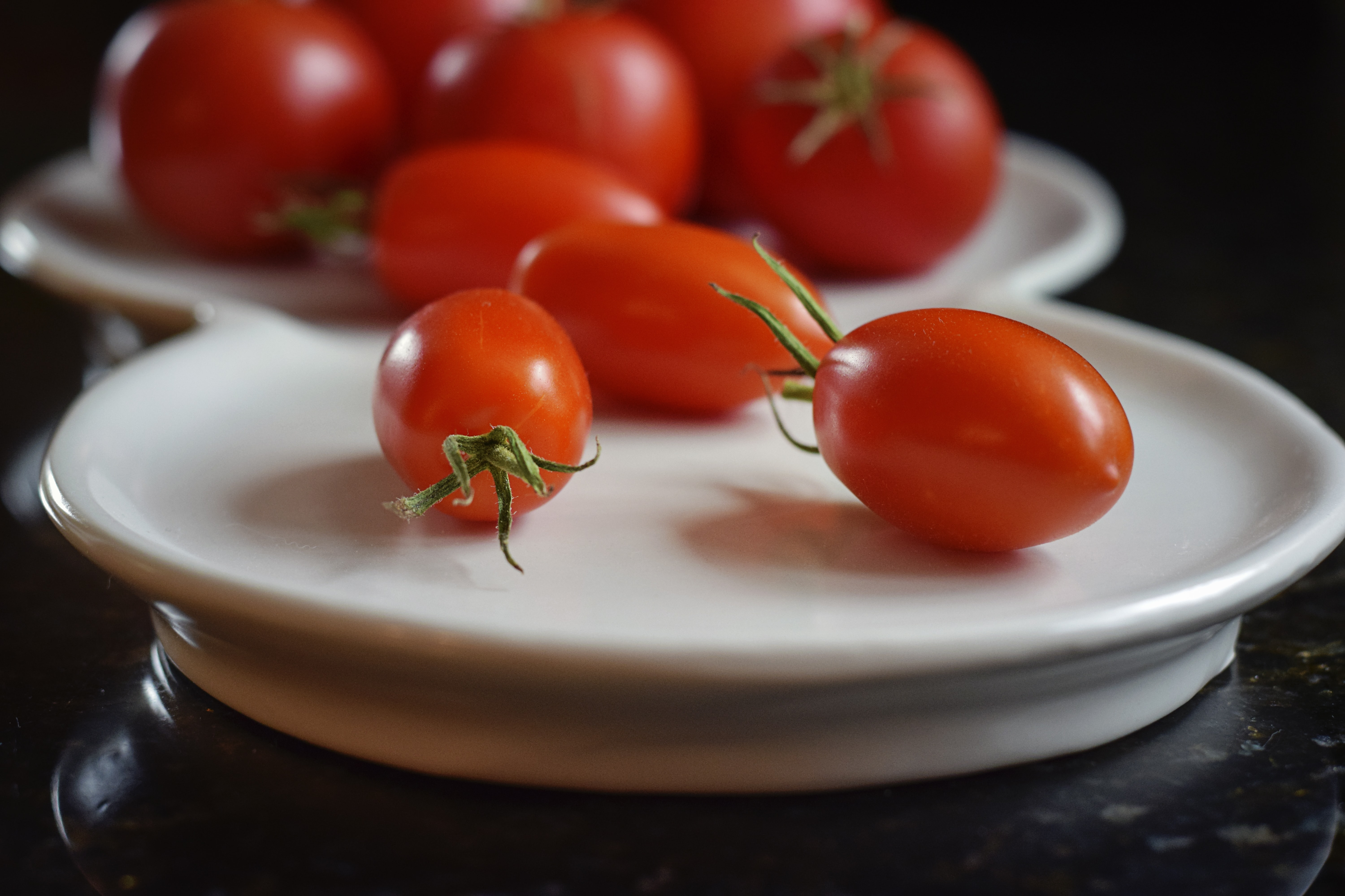 red tomatoes on white ceramic plate