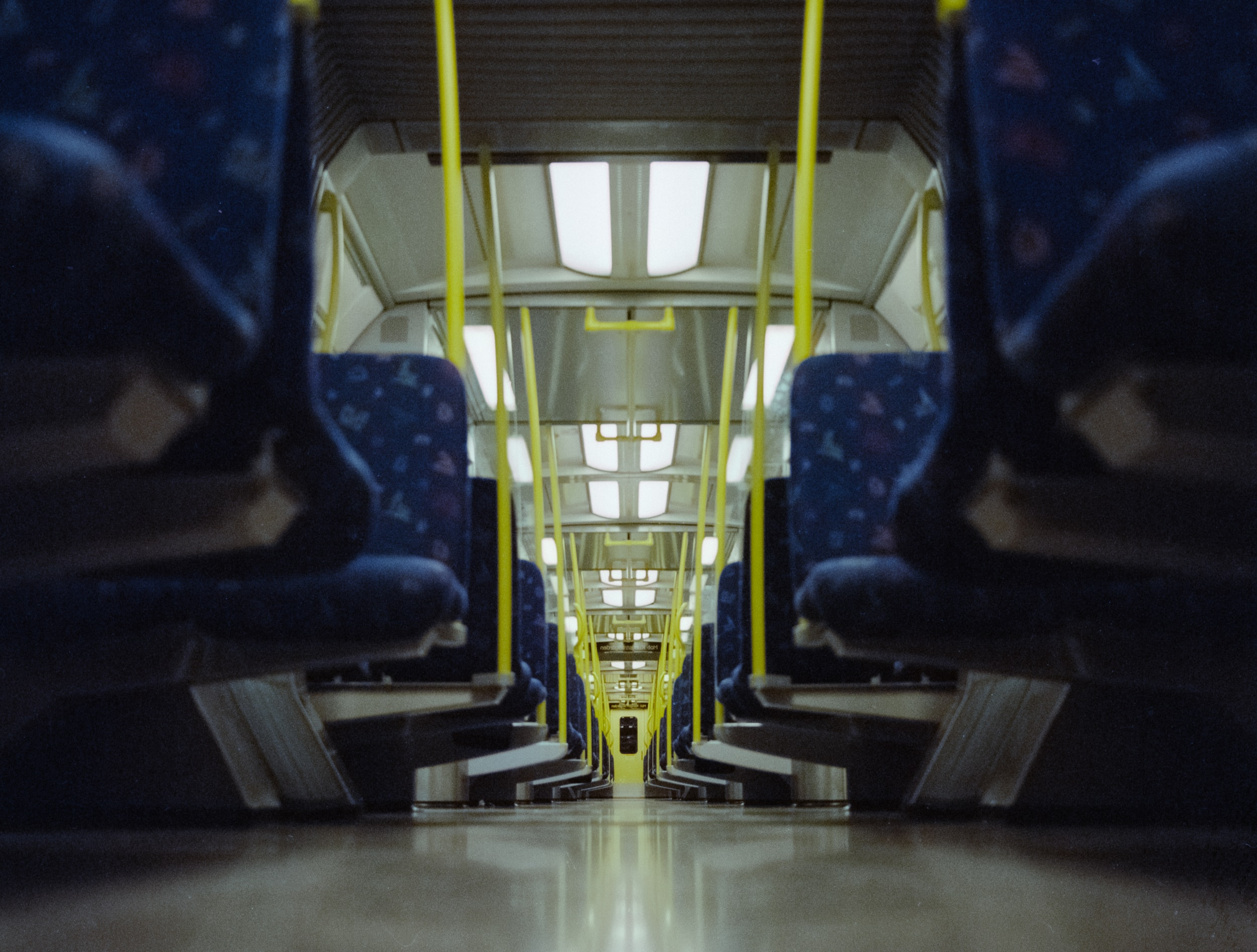 Interior shot of a lit train with dark blue seats taken from the floor