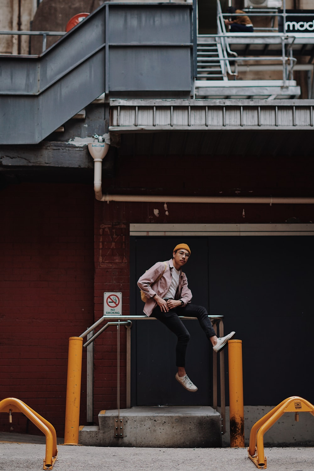 man sitting on railing in front of building