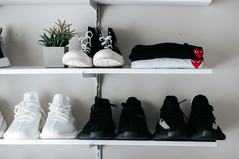 three pairs of black and white shoes on floating shelf