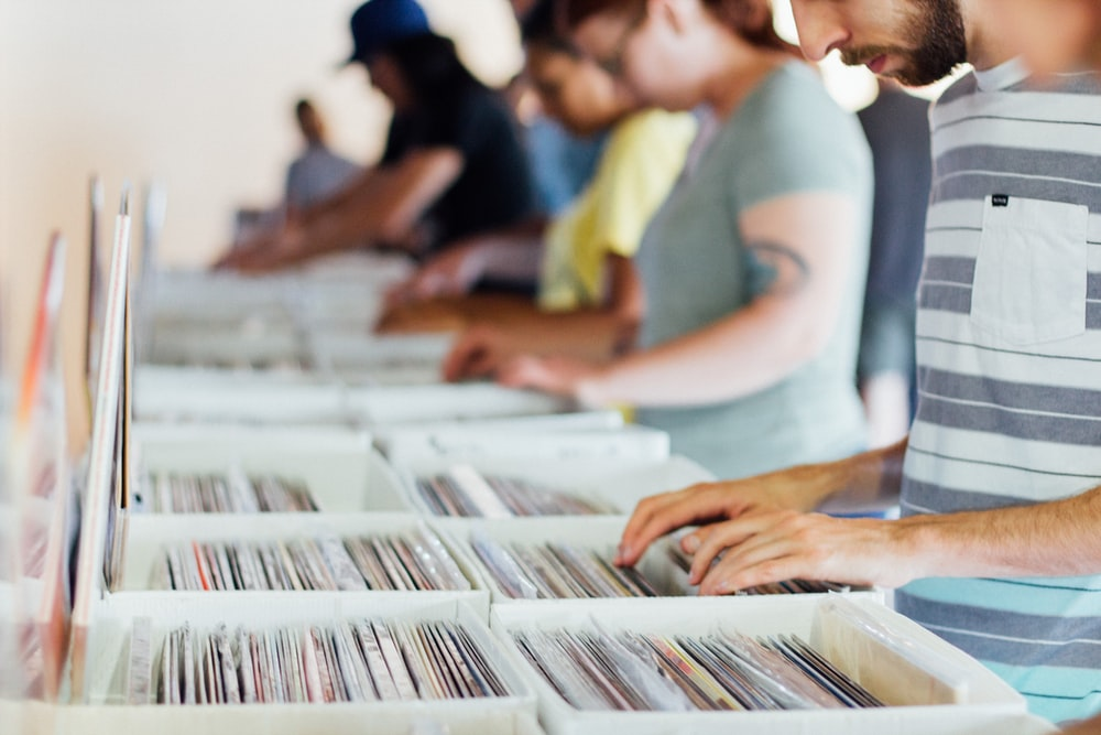 selective focus photography of group of people selecting vinyl record sleeves