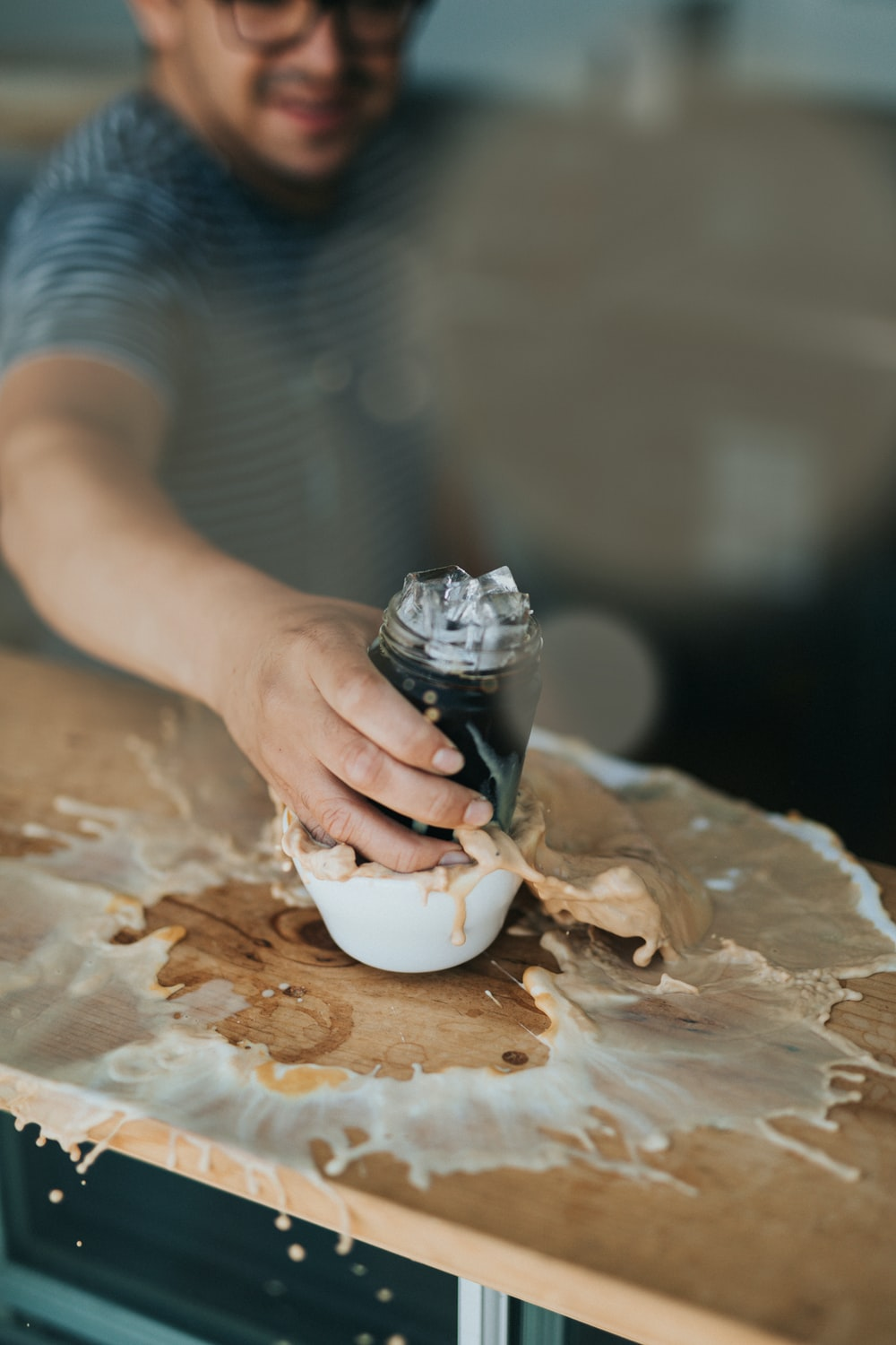 man holding clear glass jar putting on white ceramic bowl on brown wooden table