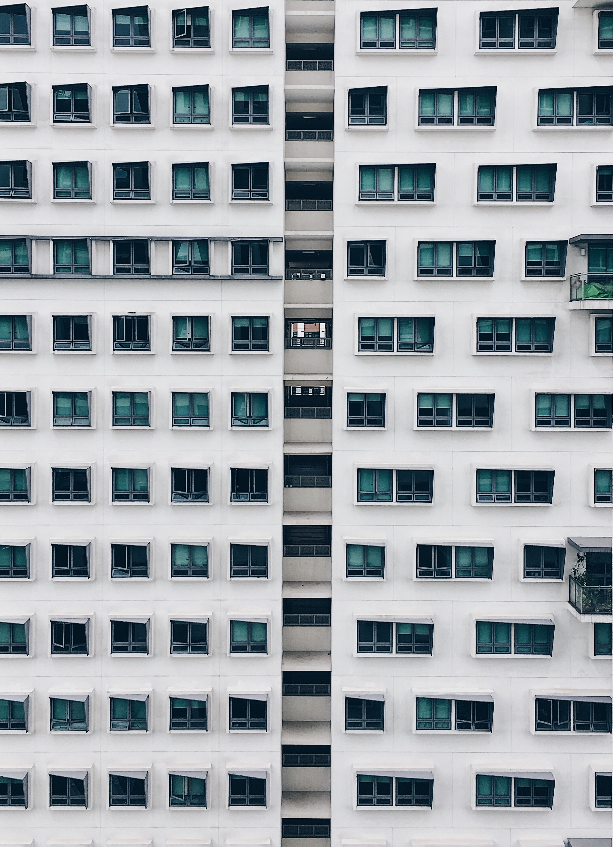 Architecture of apartment building in Singapore with white facade and light blue windows