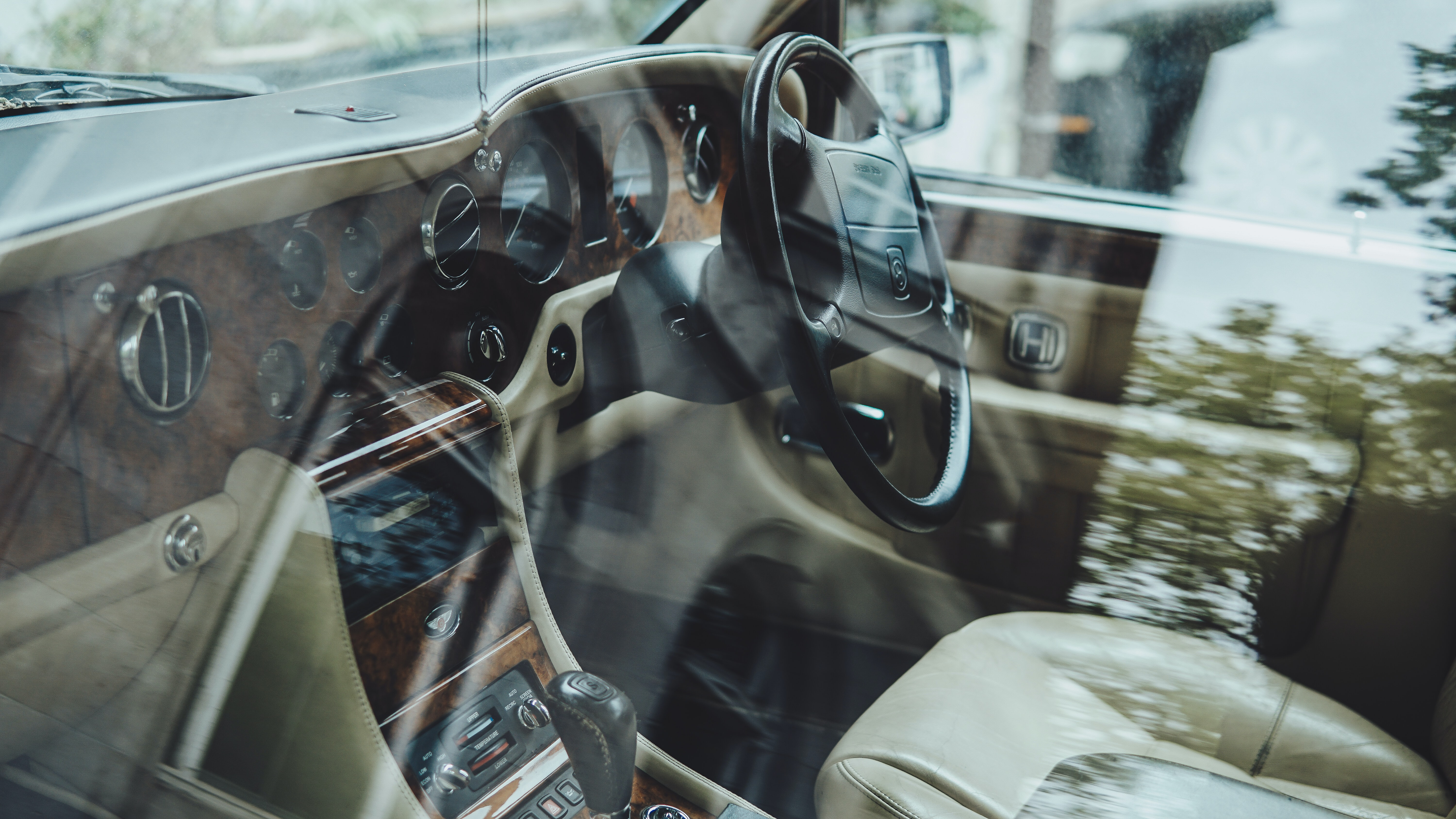 Interior of a car with wood panels and white leather trims