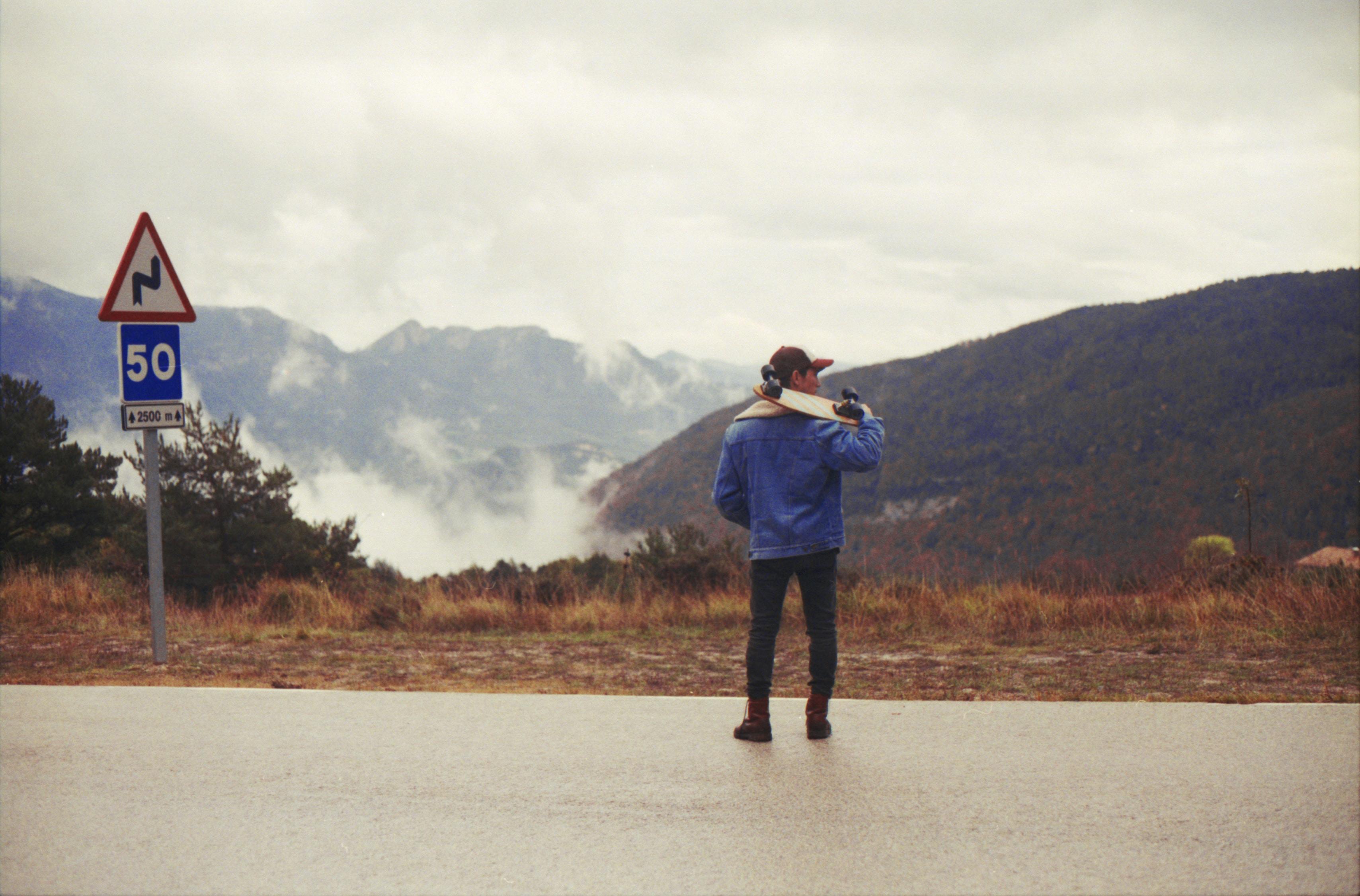 man in blue jacket carrying skateboard