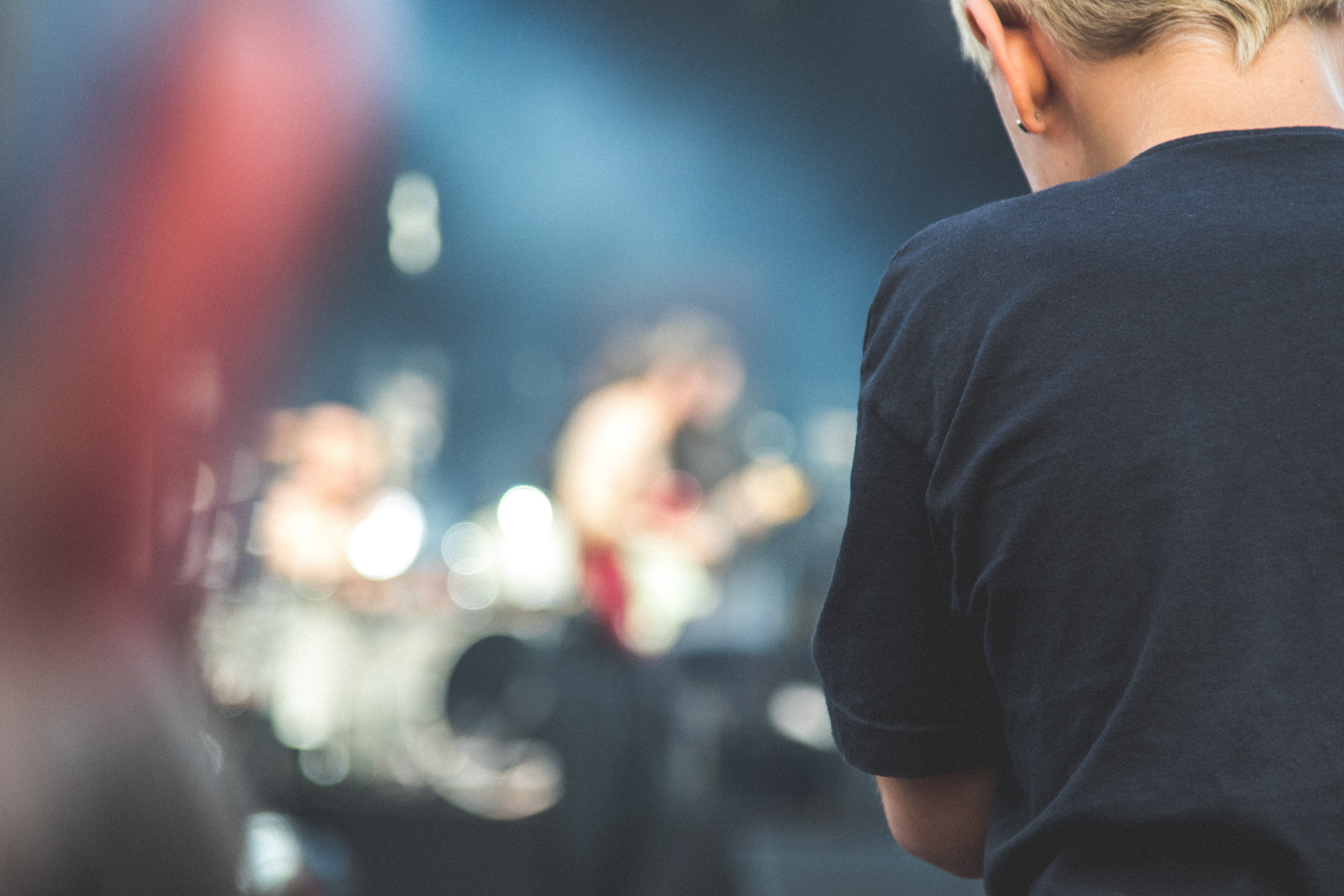 Standing behind a person with a blurry band playing on stage in the background