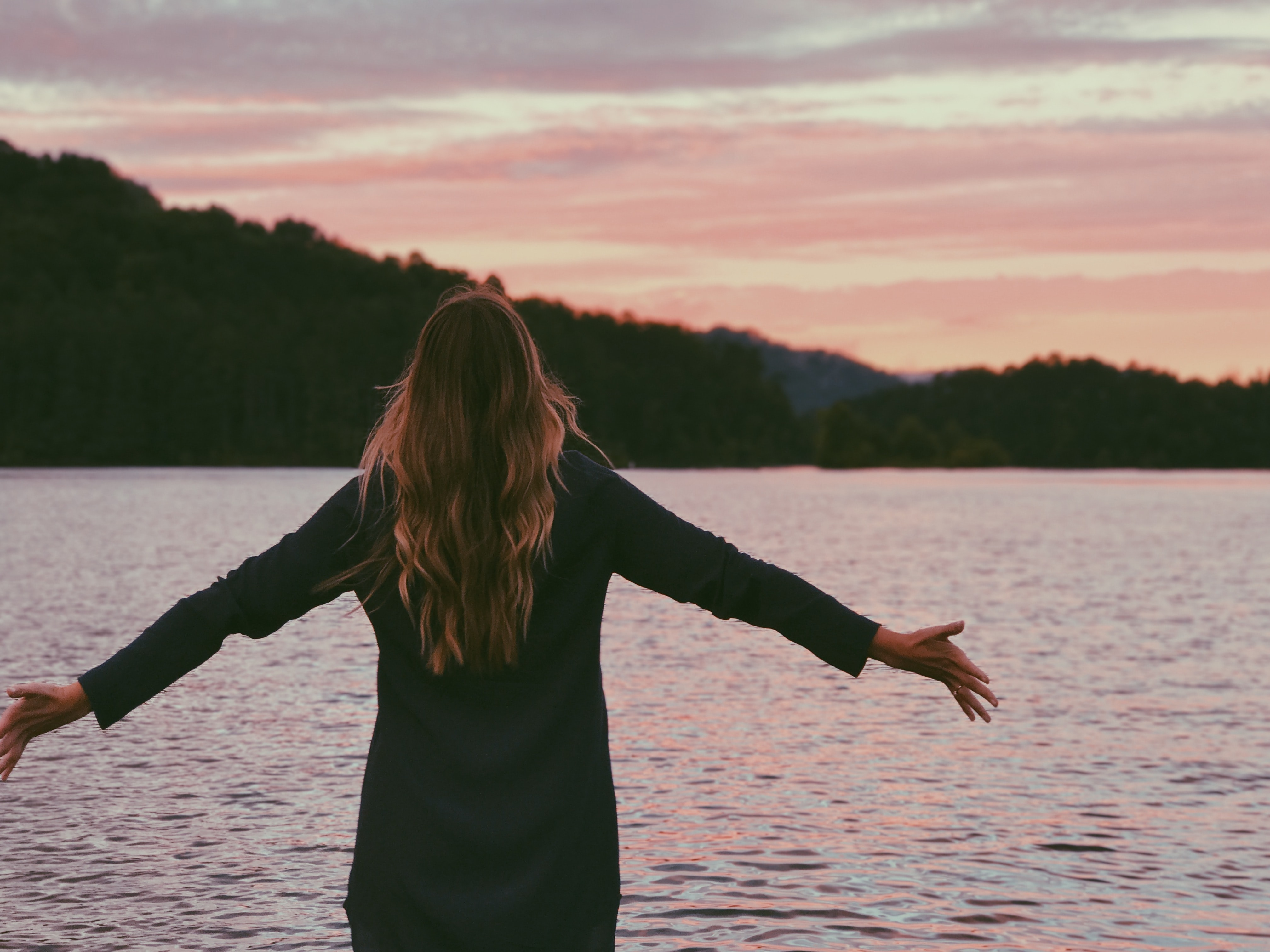 A woman faces a body of water, arms outstretched, at sunset