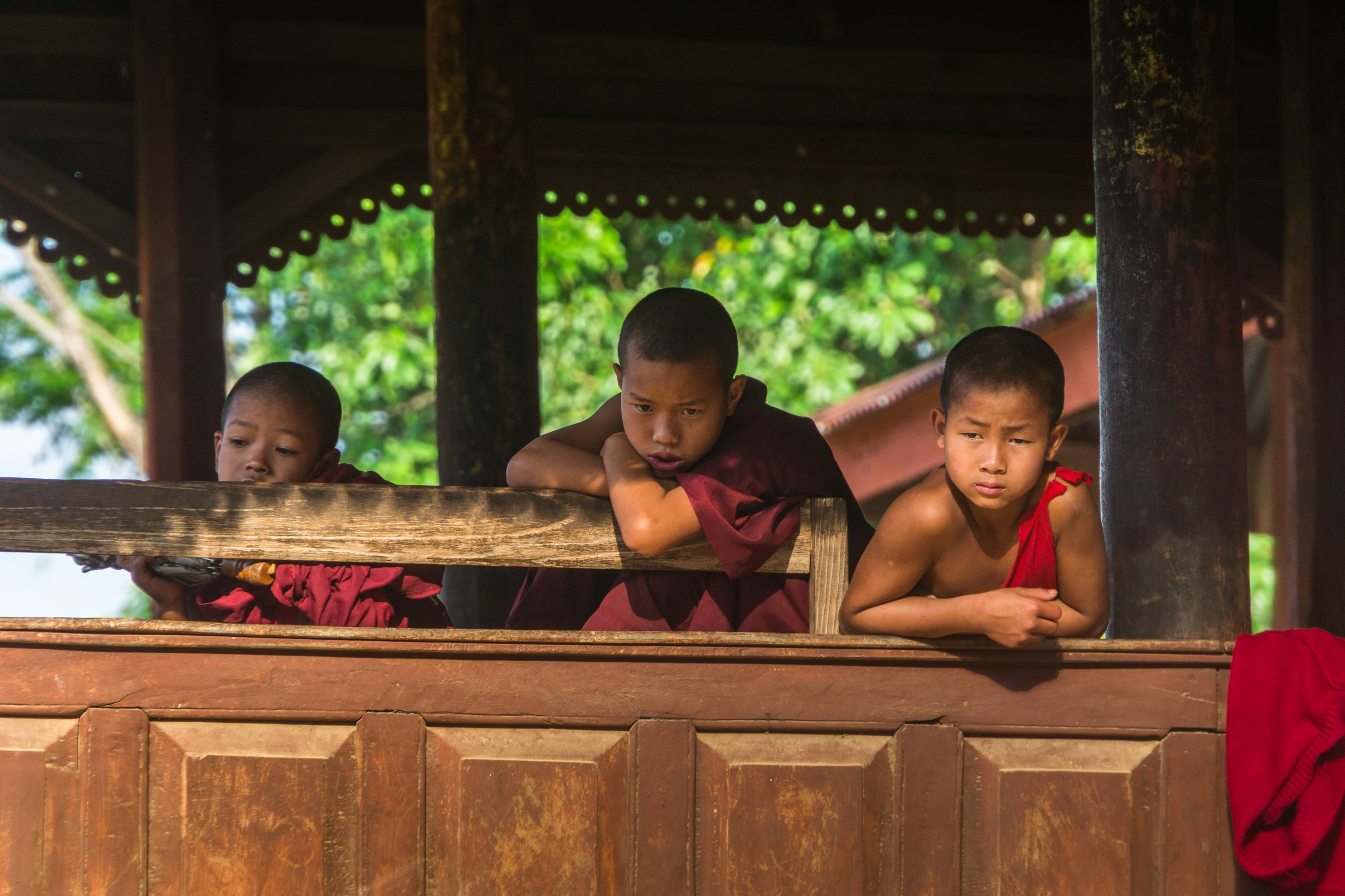 Bored children in robes lean against a temple railing in Myanmar