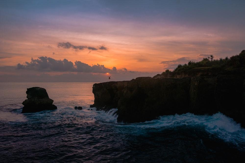 body of water splashing on rocks during golden hour