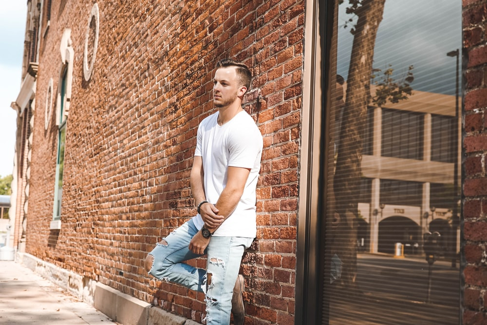 man in white crew-neck T-shirt in front of brown concrete building