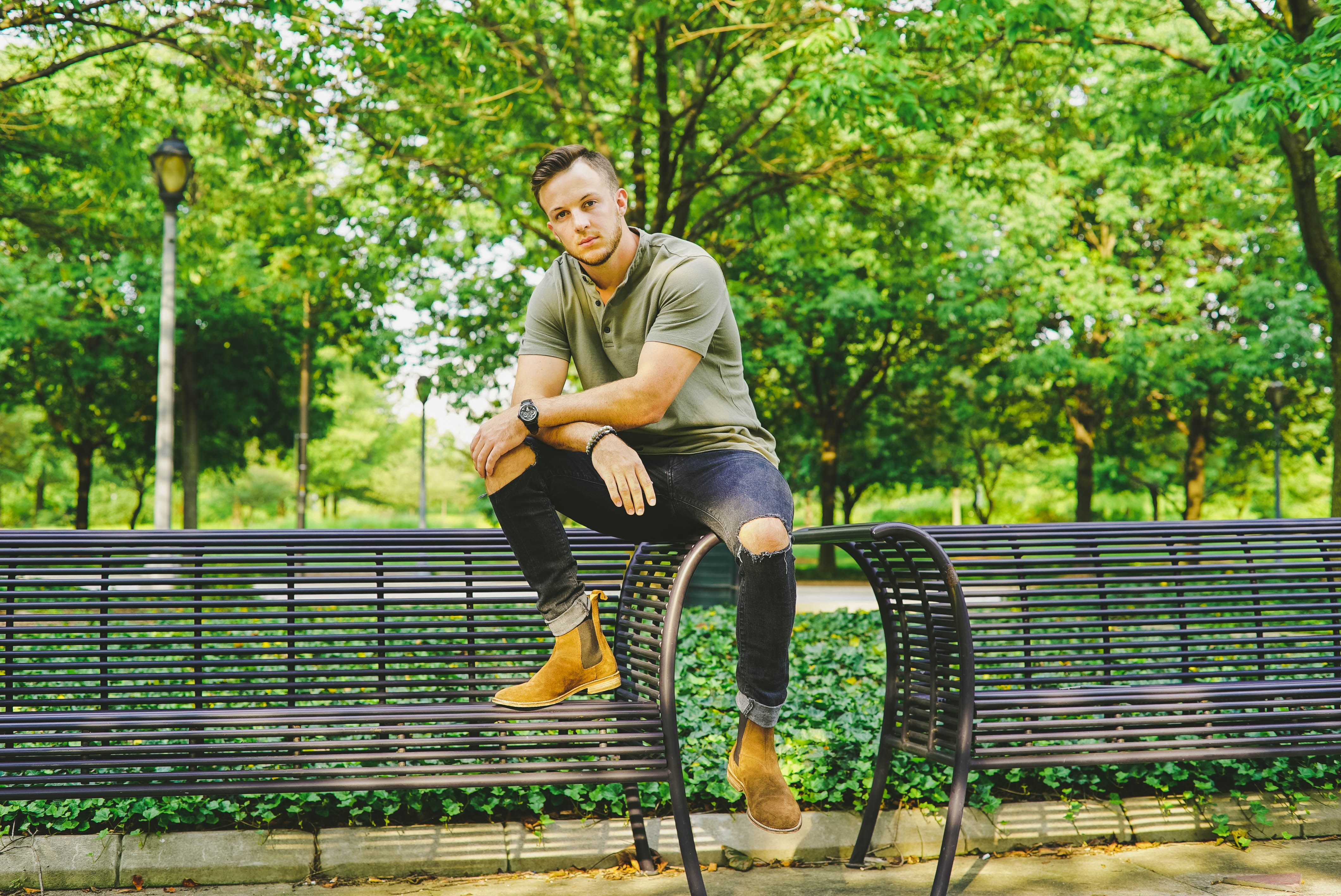 Young man in ripped jeans sitting on an empty park bench